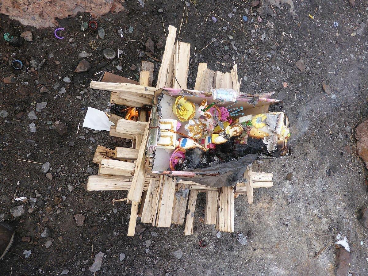 Das Bild zeigt einen kleinen Altar auf dem Kokablätter, Papiergeld und Süßigkeiten liegen und angezündet werden.