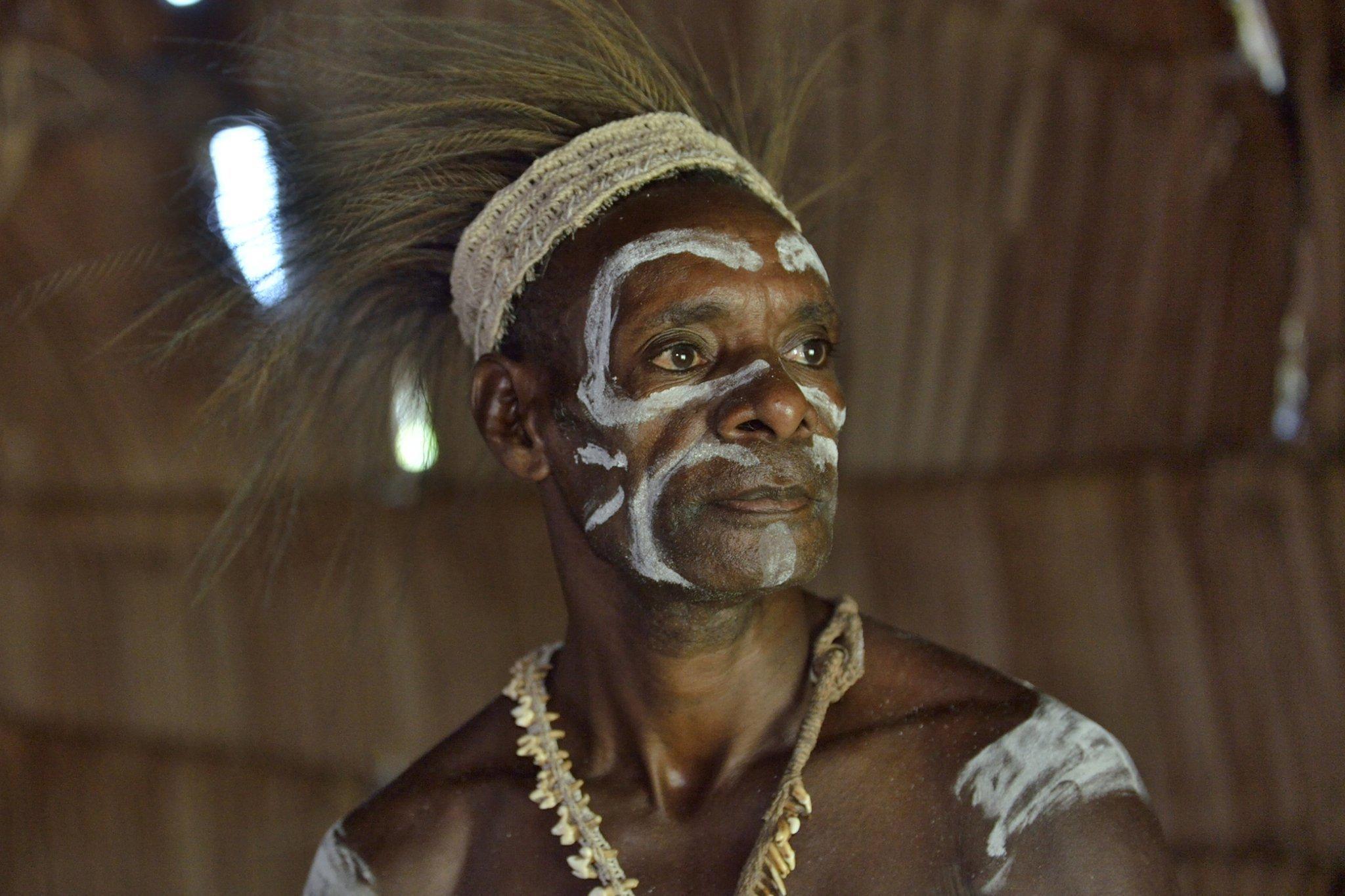 Das Bild zeigt einen Mann aus dem Volk der Asmat in Neuguinea. Er trägt eine Kette, ist im Gesicht weiß geschminkt, die Hare mit einem breiten Band nach oben gebunden, und strahlt viel Selbstbewusstsein aus. Die Papua, zu denen er gehört, tragen im Durchschnitt rund drei Prozent Erbgut der Denisova-Menschen in sich und profitieren davon.