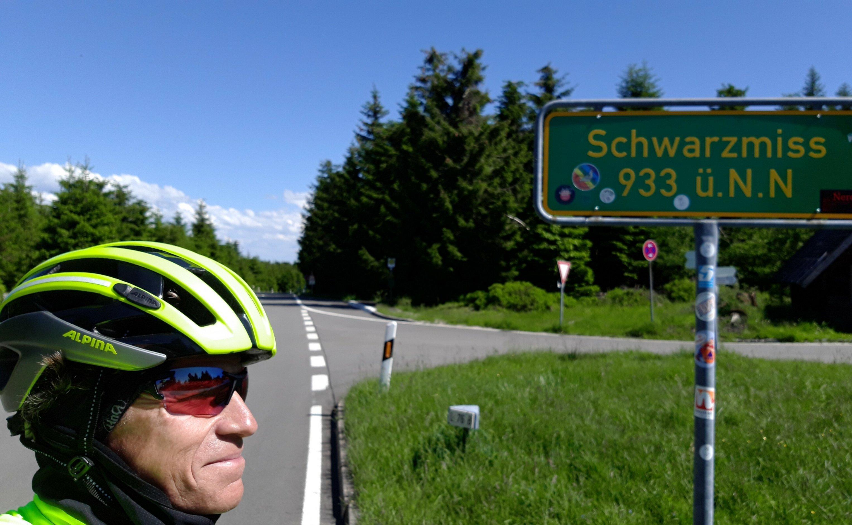 Der Autor Martin C Roos mit Radhelm posiert neben dem grünen Schild, dass die Passhöhe benennt.