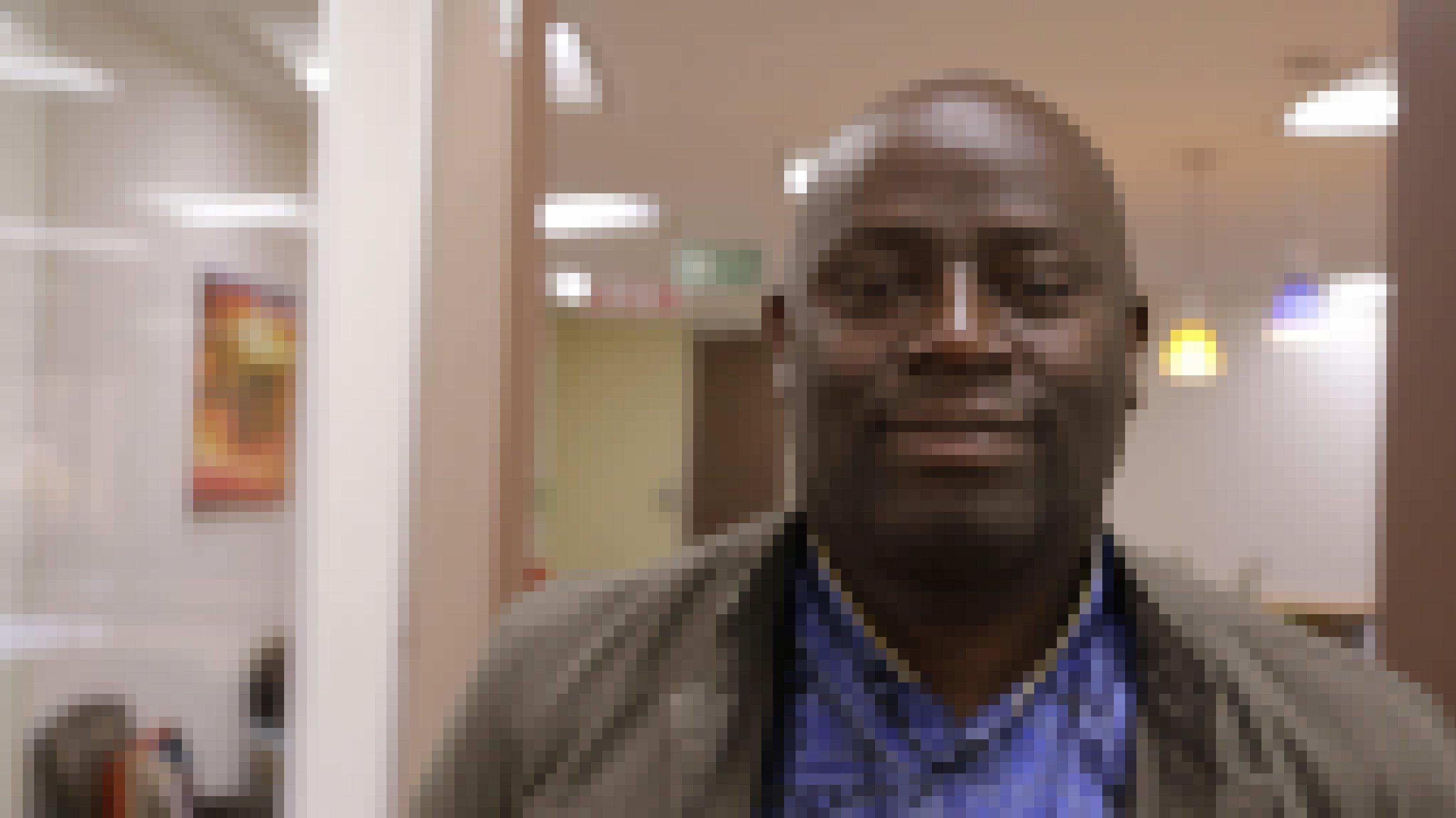 Paul Mulindwa trägt ein blaues Top und eine Jacke darüber, er schaut direkt in die Kamera, der Raum dahinter ist verschwommen