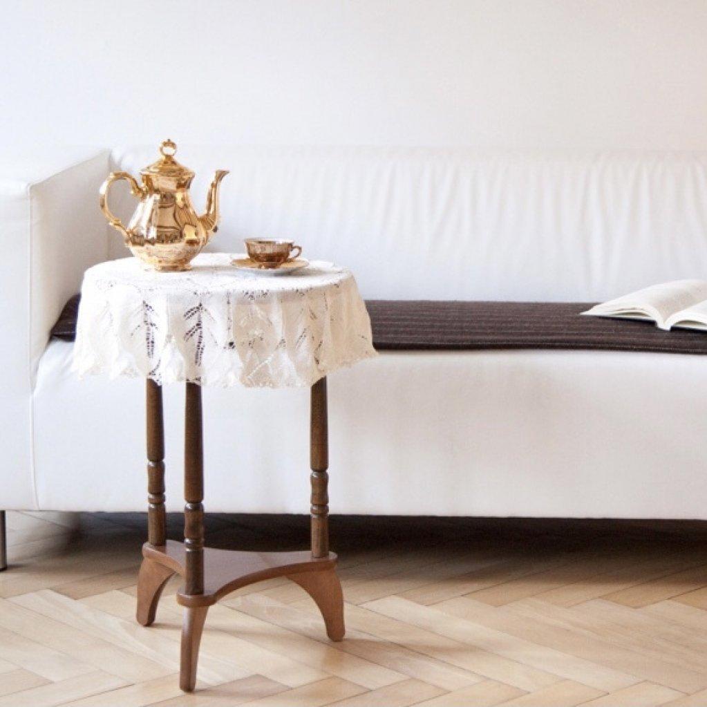 Das Foto zeigt ein weißes Sofa, auf dem ein aufgeschlagenes Buch liegt. Vor dem Sofa steht ein rundes Holztischchen, auf dem eine goldene Kaffeekanne und eine goldene Tasse stehen. Das Bild strahlt Ruhe aus und lädt zum Innehalten ein.