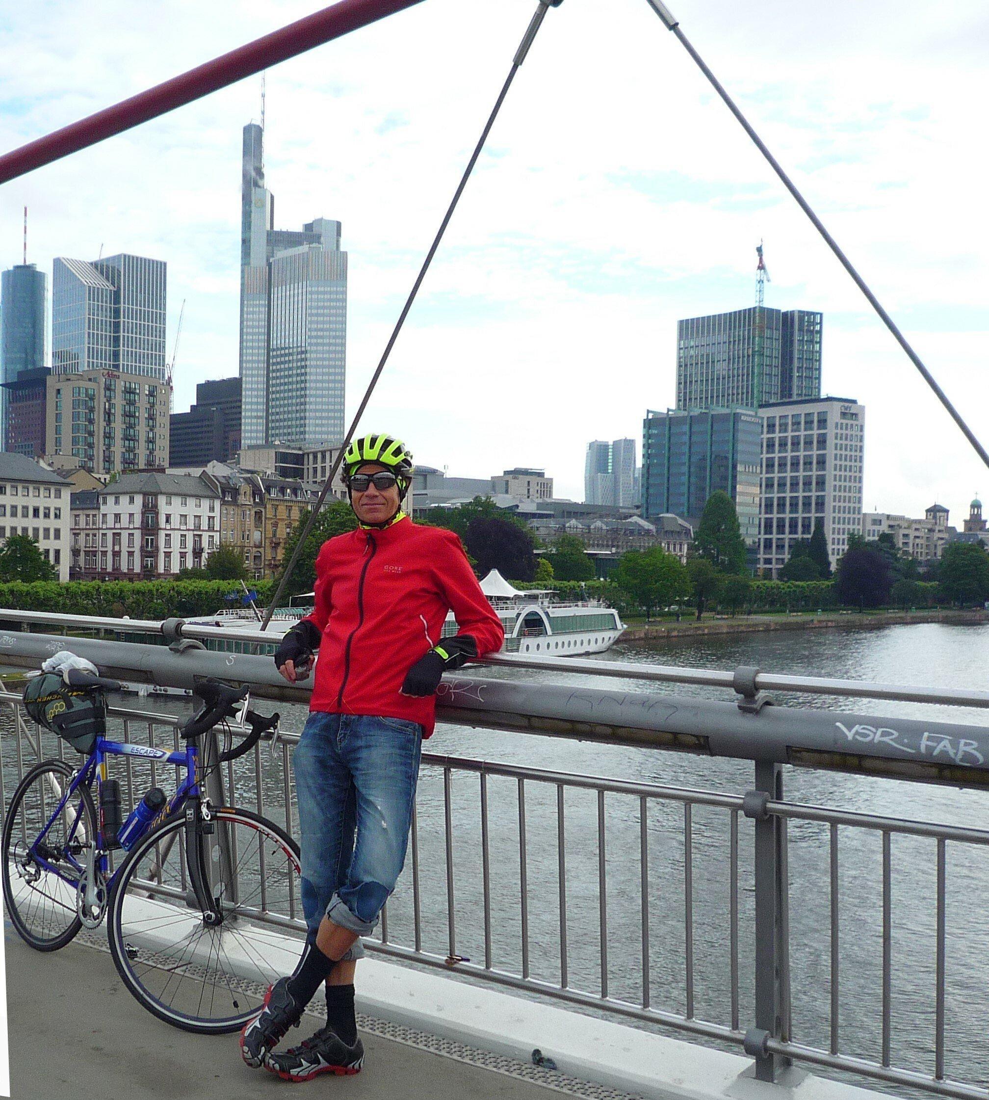 Martin C Roos steht mit seinem Rennrad am Geländer des Holbeinstegs, hinter ihm der Main vor der Skyline Frankfurts.
