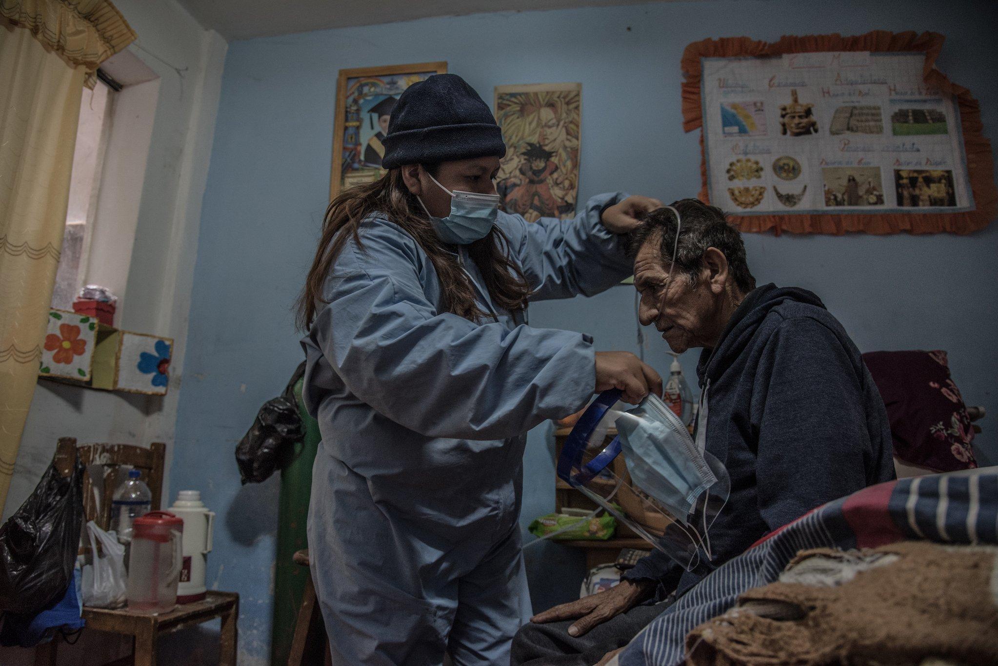 Eine Frau mit langen Haaren unter einer Mütze, in einem blauen Ganzkörperanzug aus Plastik und mit Mundschutz hilft einem älteren Mann. Sie nimmt dafür seinen Mundschutz und das transparente Visier ab. Der Mann sitzt in seinem Schlafzimmer auf dem Bett. Hinter der Frau ist die grüne Gasflasche zu sehen, die fast so groß wie sie ist.