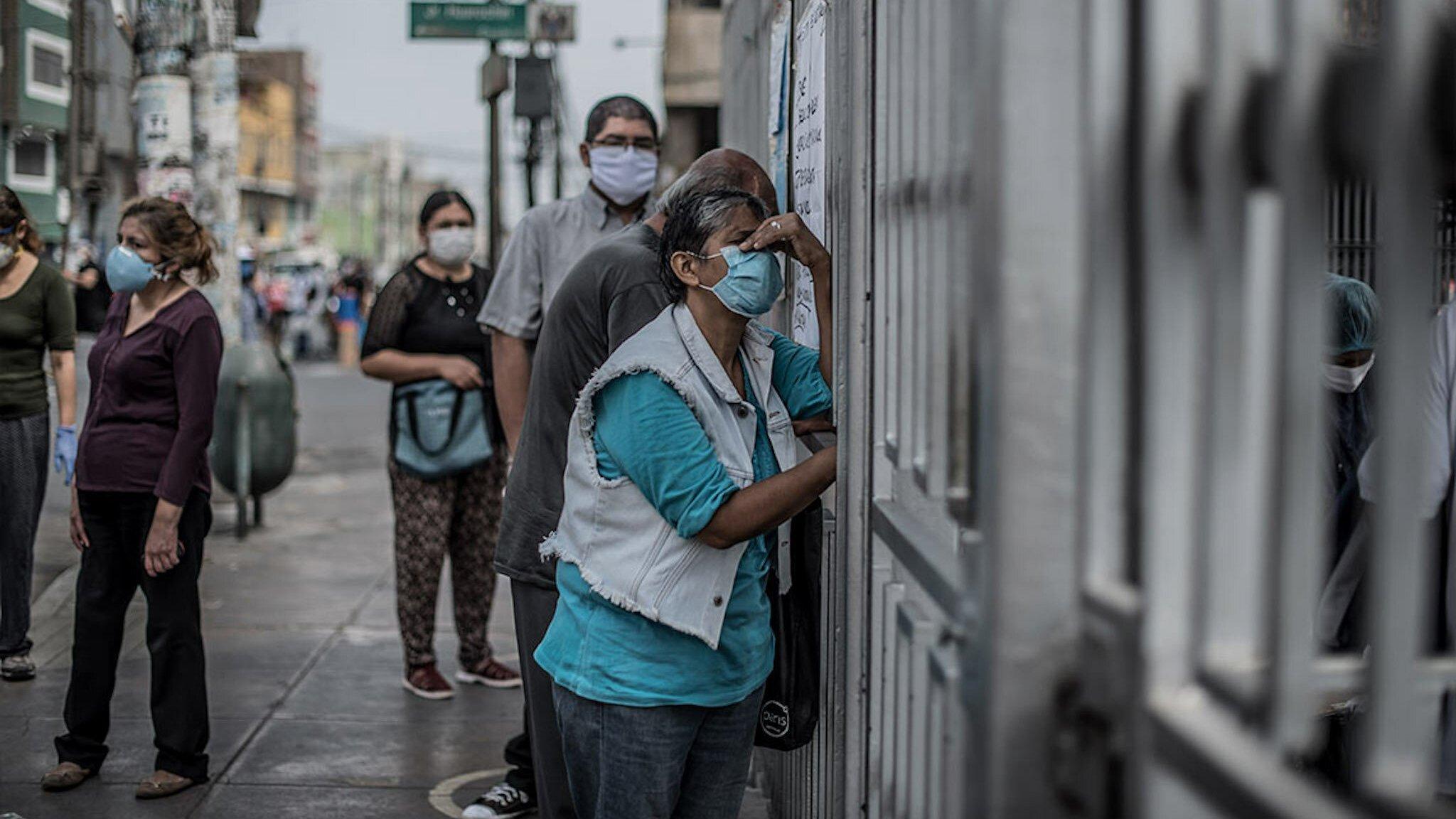 Die Frau hat graue Haare und trägt einen Mundschutz. Sie lehnt sich an das Metallgitter-Tor. Hinter ihr auf der Straße stehen weitere Menschen an.
