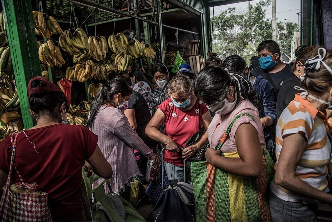 Peruanische Frauen stehen dicht gedrängt mit Tragetaschen und Wägelchen vor einem Bananenstand in einer Markthalle in Lima.