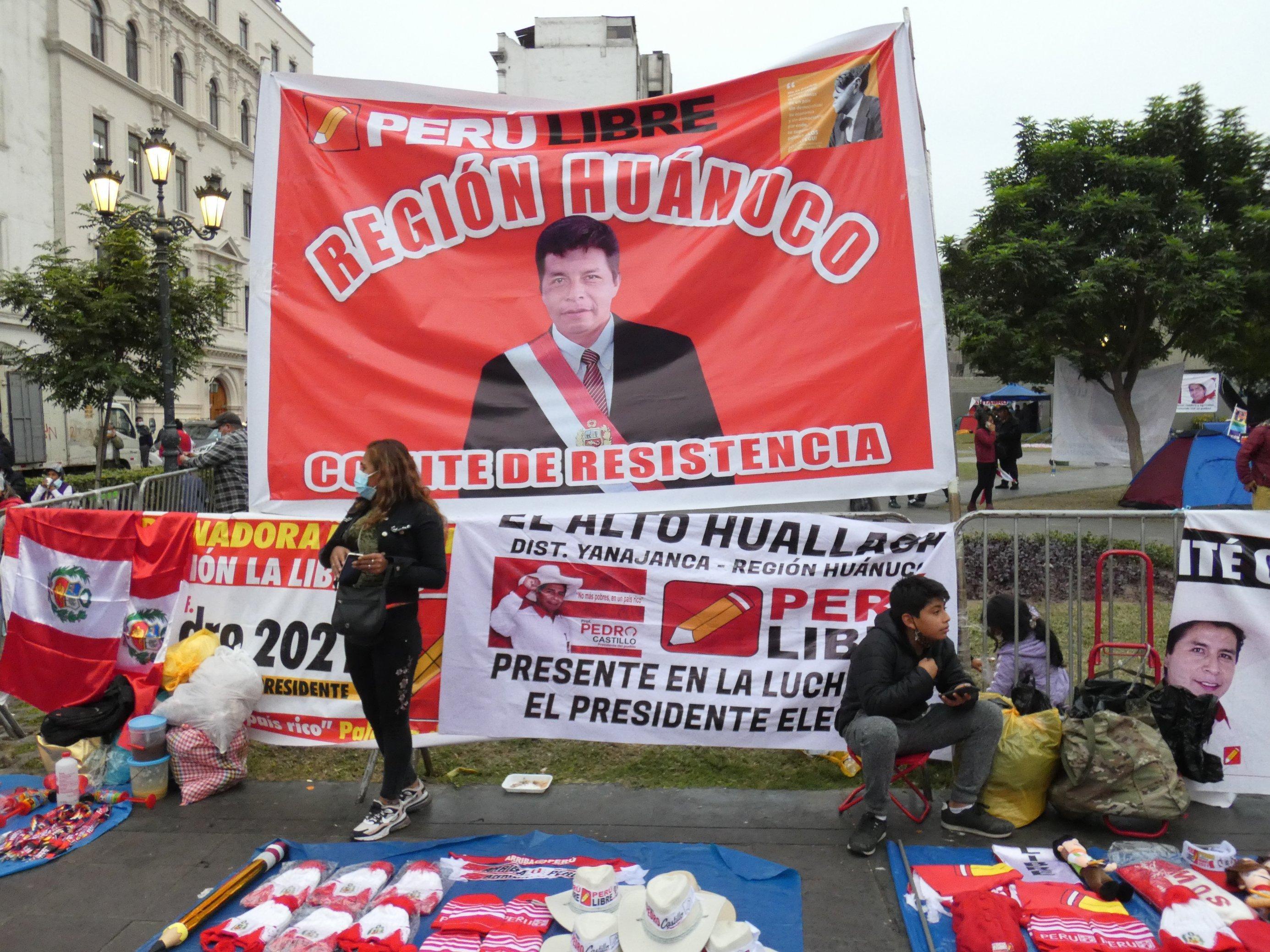 Große rote Banderole, darauf ein Mann mit einer Präsidentenschärpe. Auf dem Boden davor werden Devotionalien verkauft.