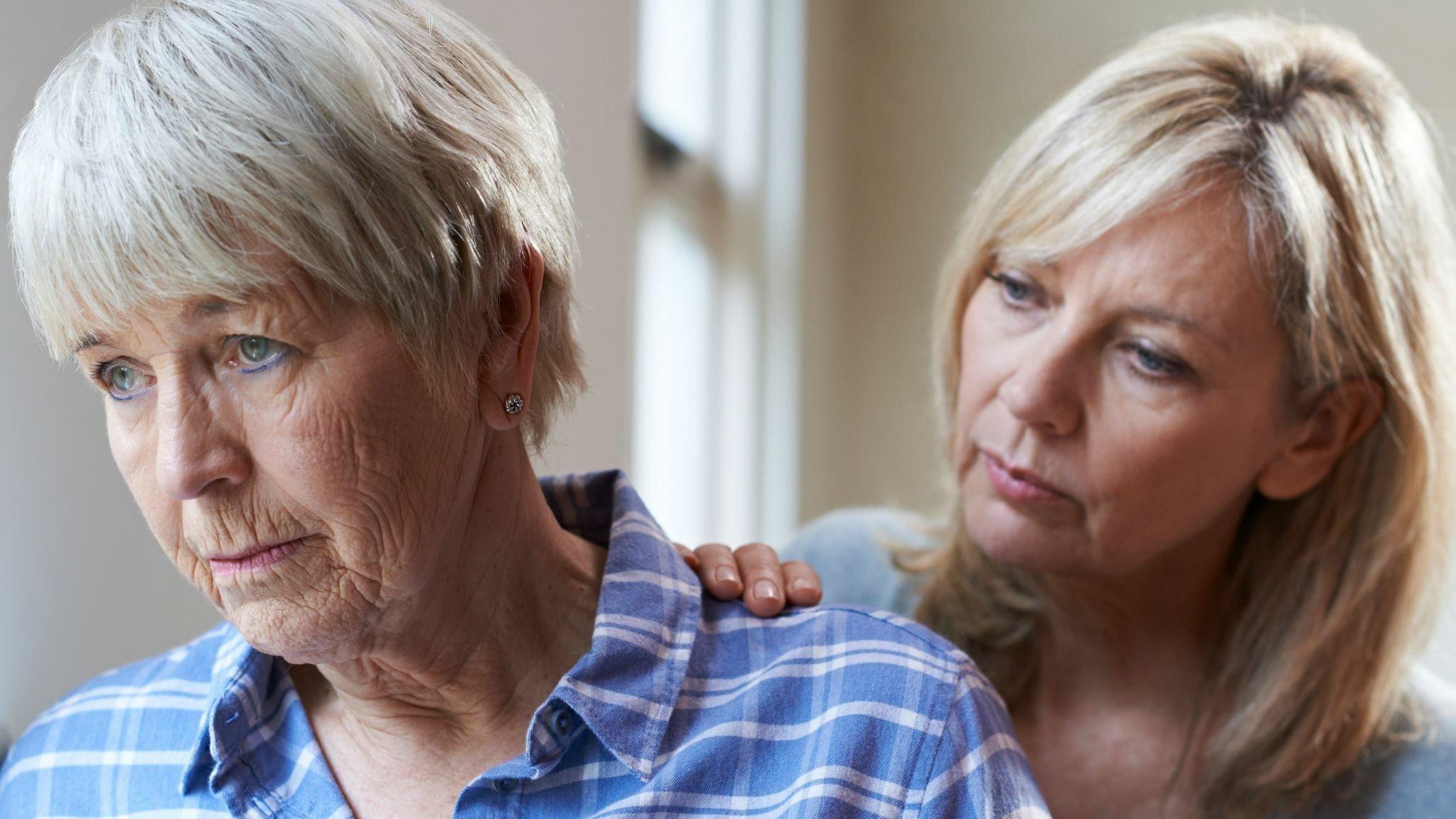 Frau legt alter Mutter die Hand auf die Schulter. Sie kümmert sich während der Corona-Pandemie alleine um die Pflege.