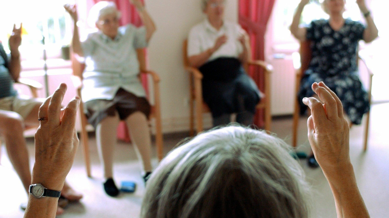 In einem Altenheim sitzen Senioren im Kreis und machen gemeinsam Gymnastik.