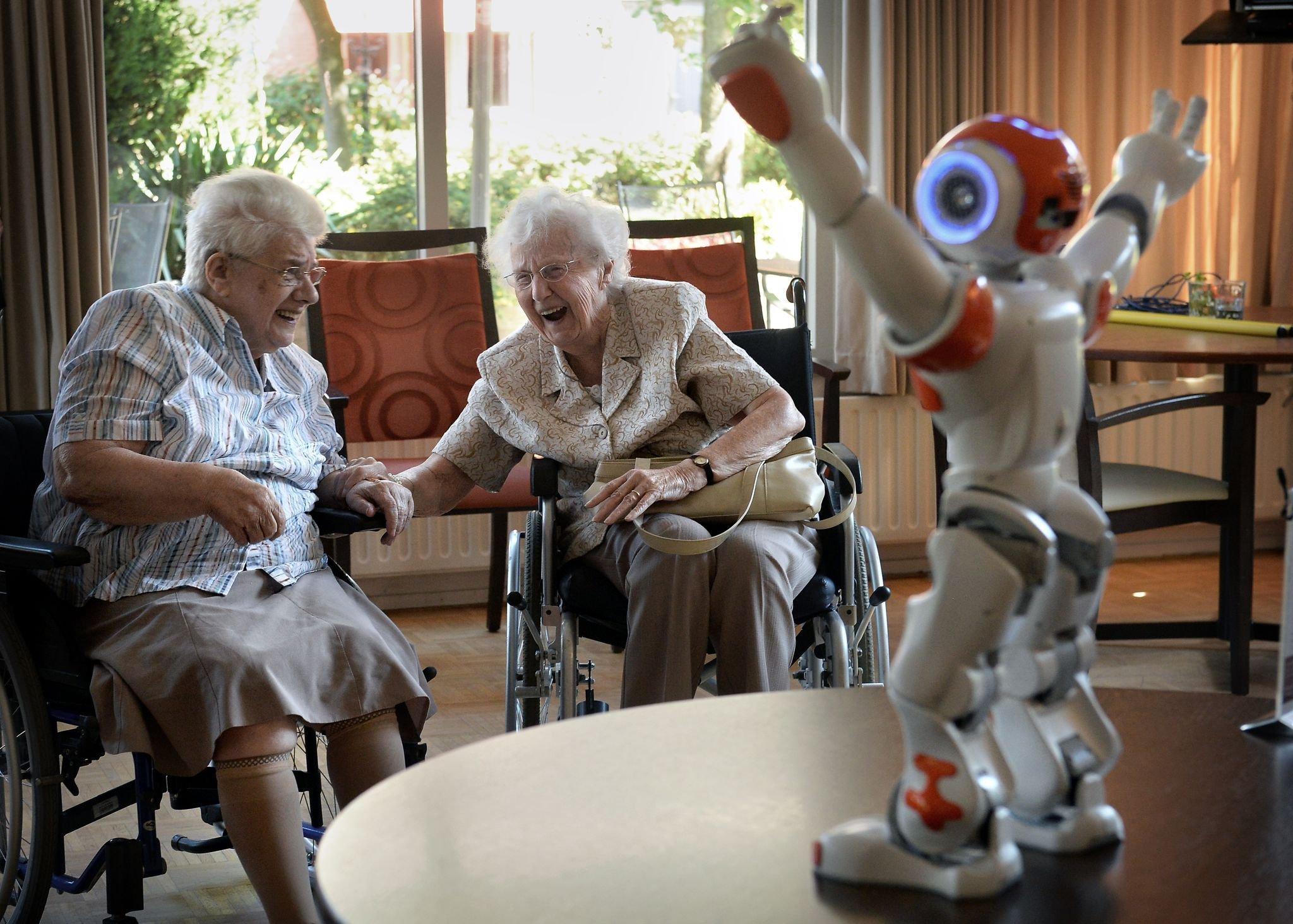 Zora ähnelt einem menschlichen Körper in Puppengröße. Sie hebt die Arme, um zwei alte Frauen im Rollstuhl zu unterhalten.