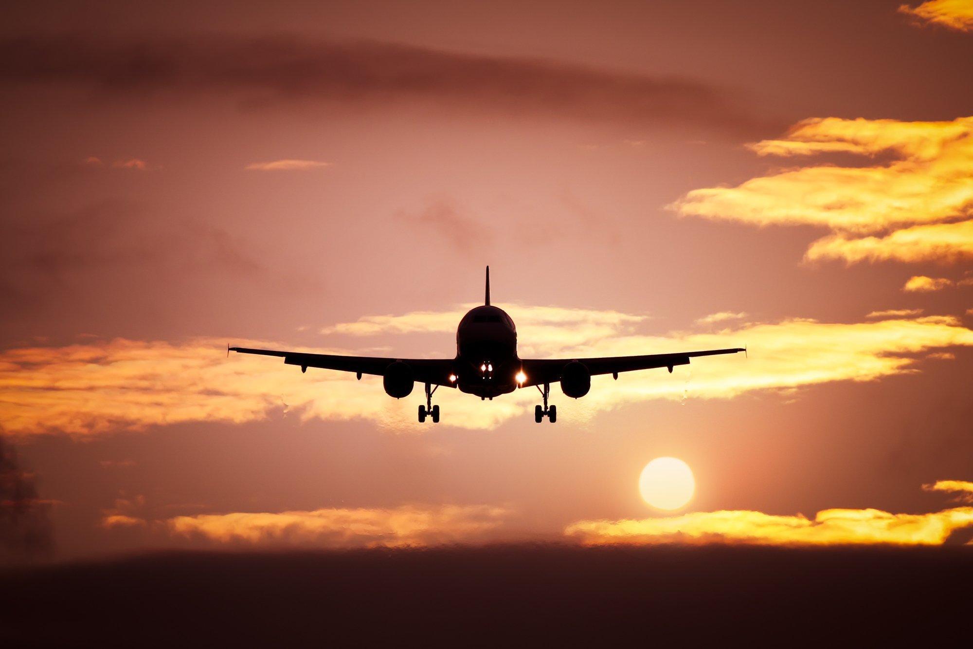 Ein Flugzeug im Start Richtung Sonnenuntergang.