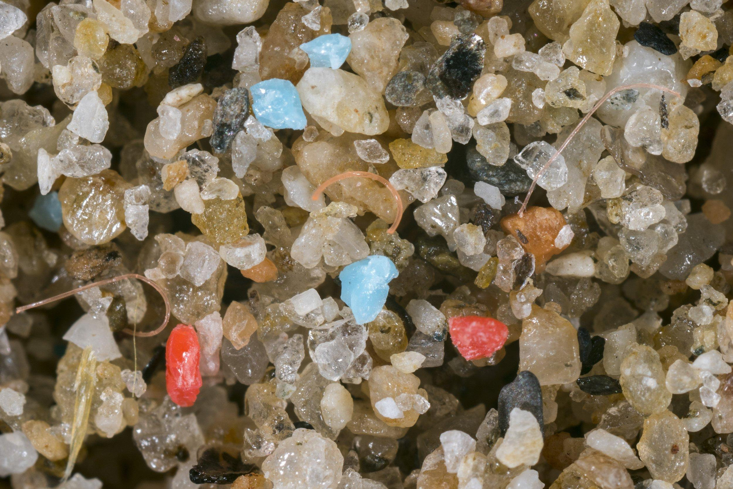 Kleinste Plastikteile zwischen Sandkörnern.