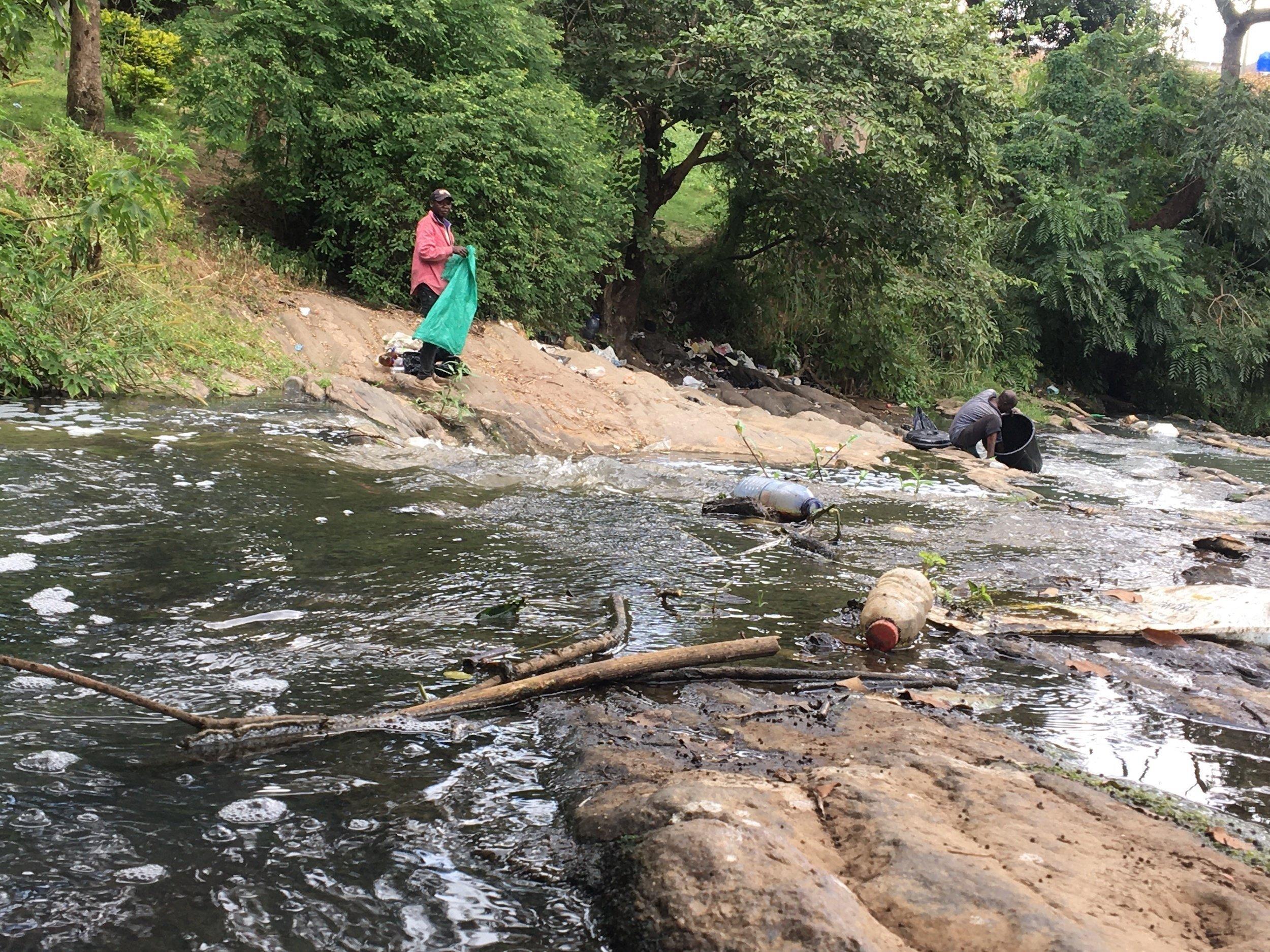 Zwei Männer an einem mit Plastikmüll verschmutzten Fluss in Malawi. Einer hat eine Mülltüte in der Hand, der andere sammelt den Abfall ein.