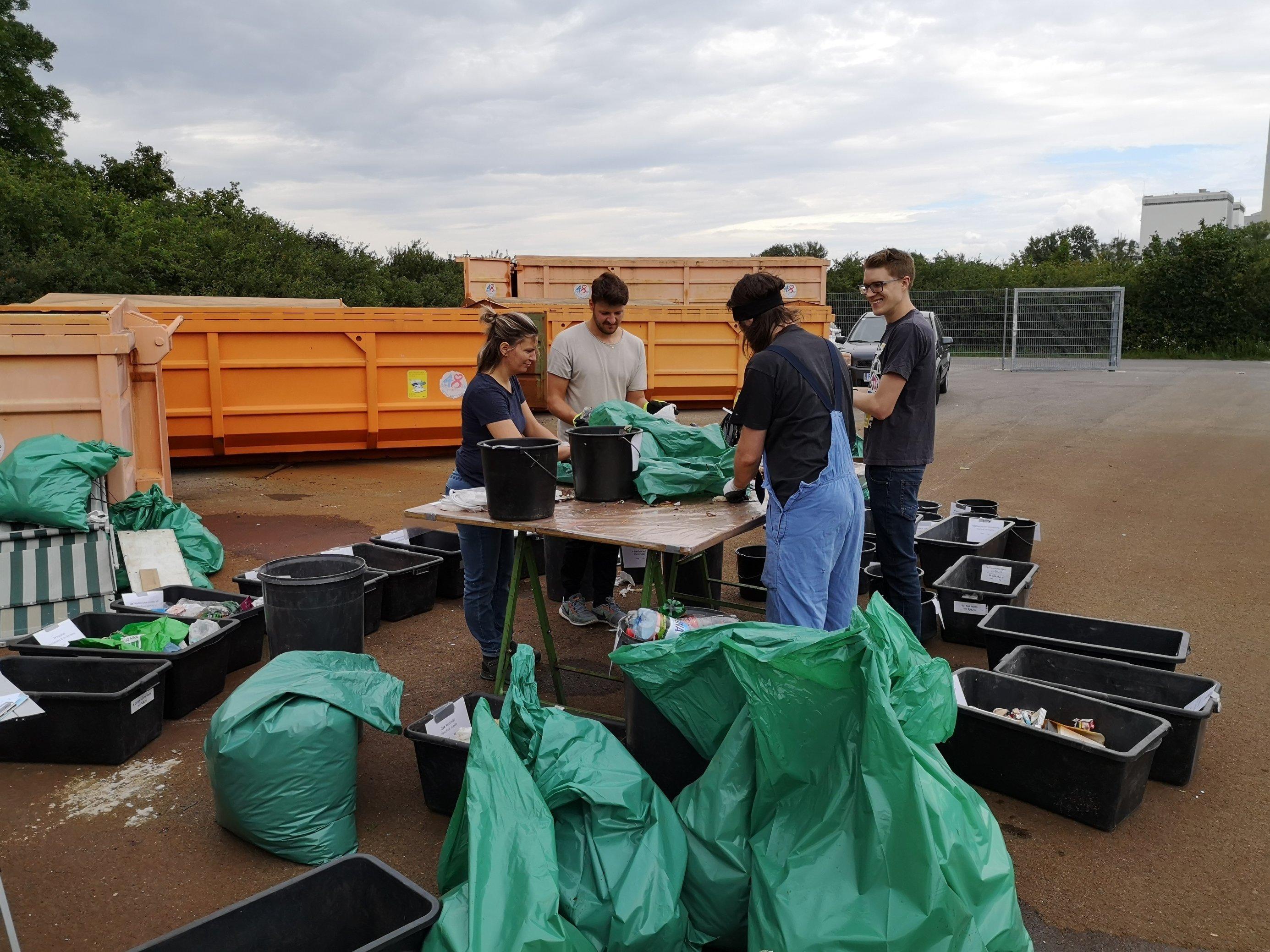 Forscherinnen und Forschern sortieren im Freien Plastikmüll in verschiedene Behälter.