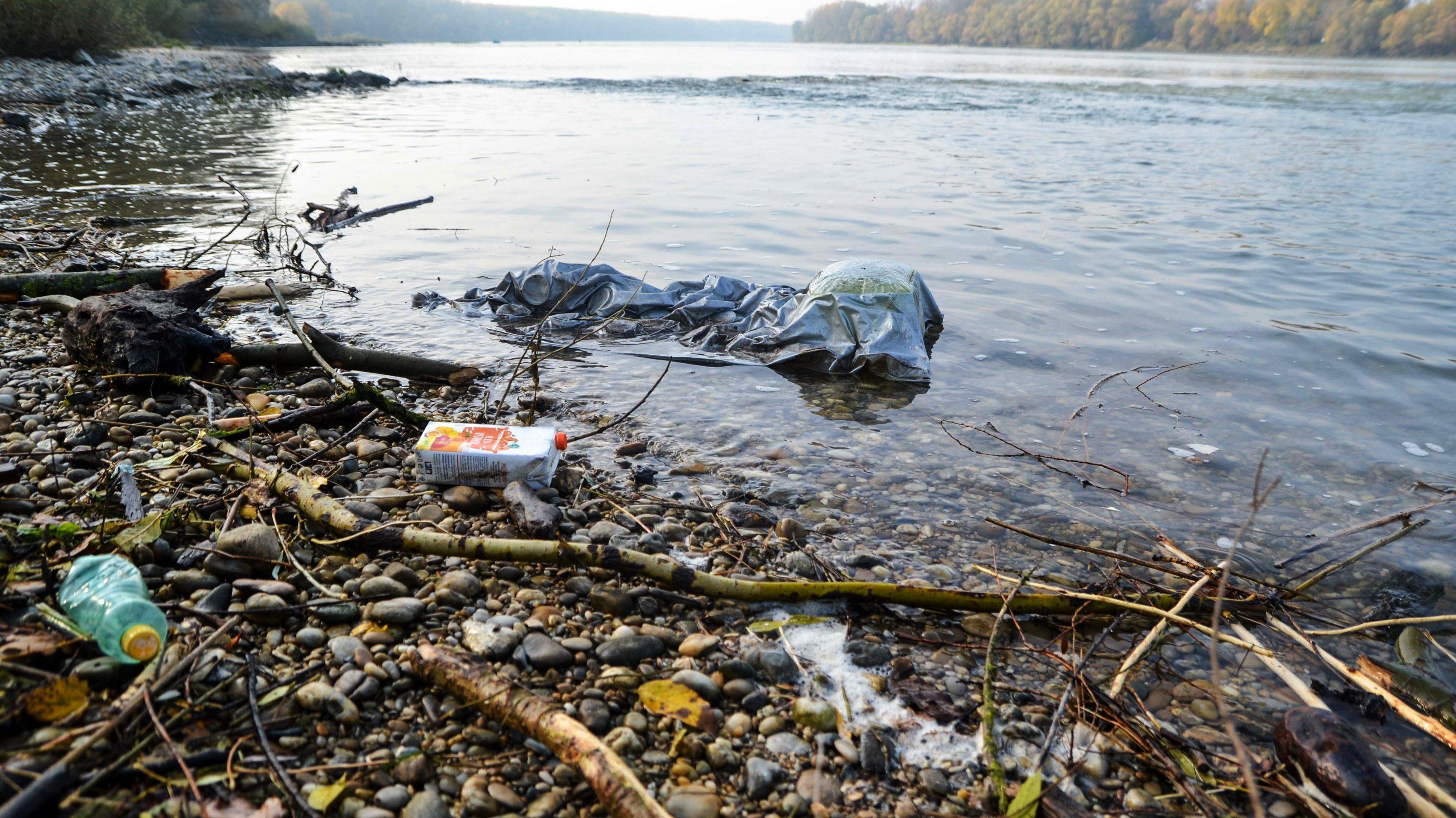 Schotter-Ufer der Donau im Bereich der Au mit Plastikabfällen.