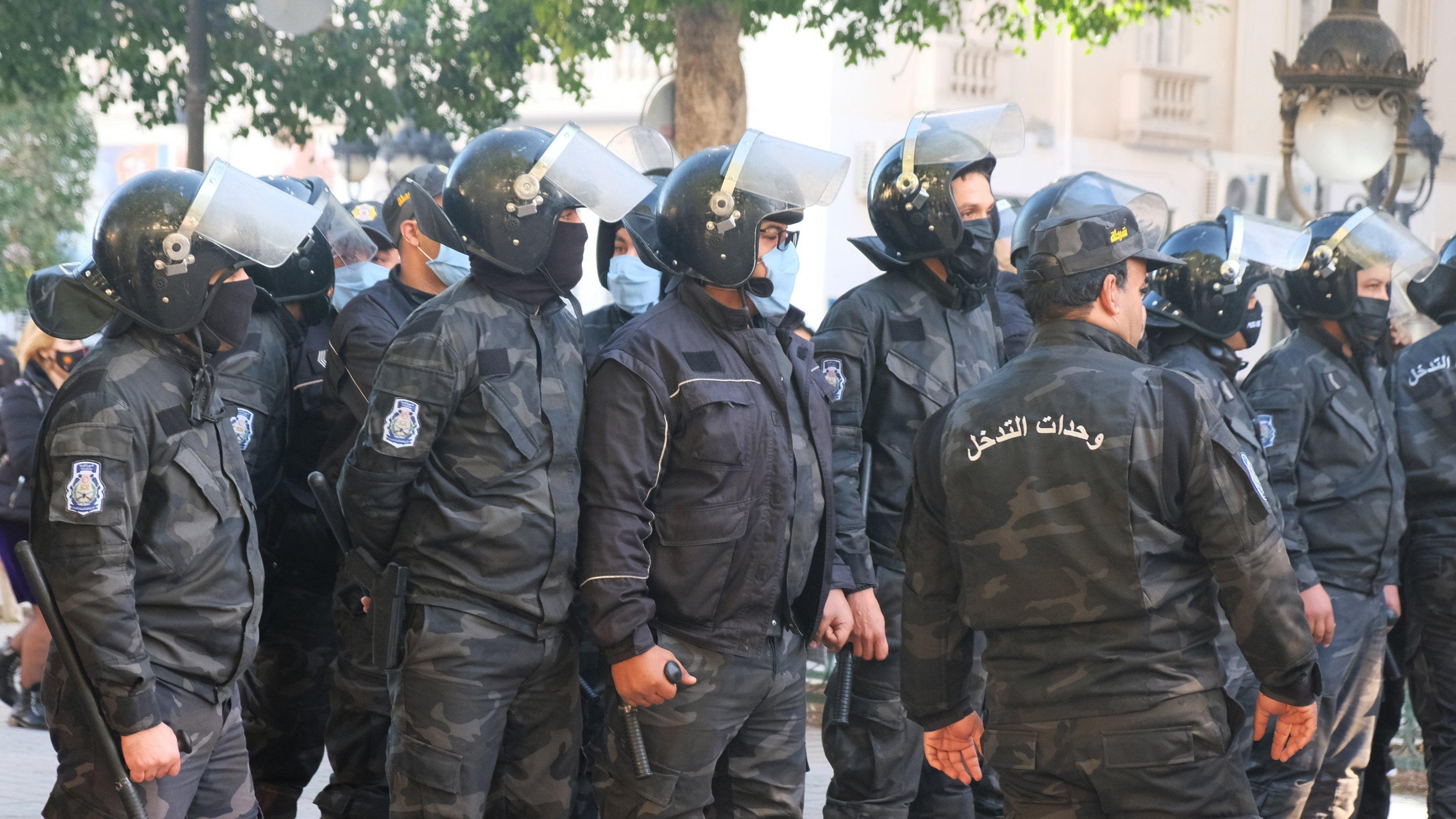 Reihe von Polizisten in schwarzer Uniformen mit Helmen, Schlagstöcken und Gesichtsmasken
