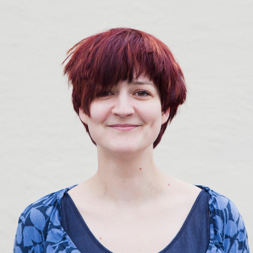 Das Foto zeigt die freie Journalistin Katharina Wojczenko, eine Frau mit kurzen, sehr rot gefärbten Haaren.