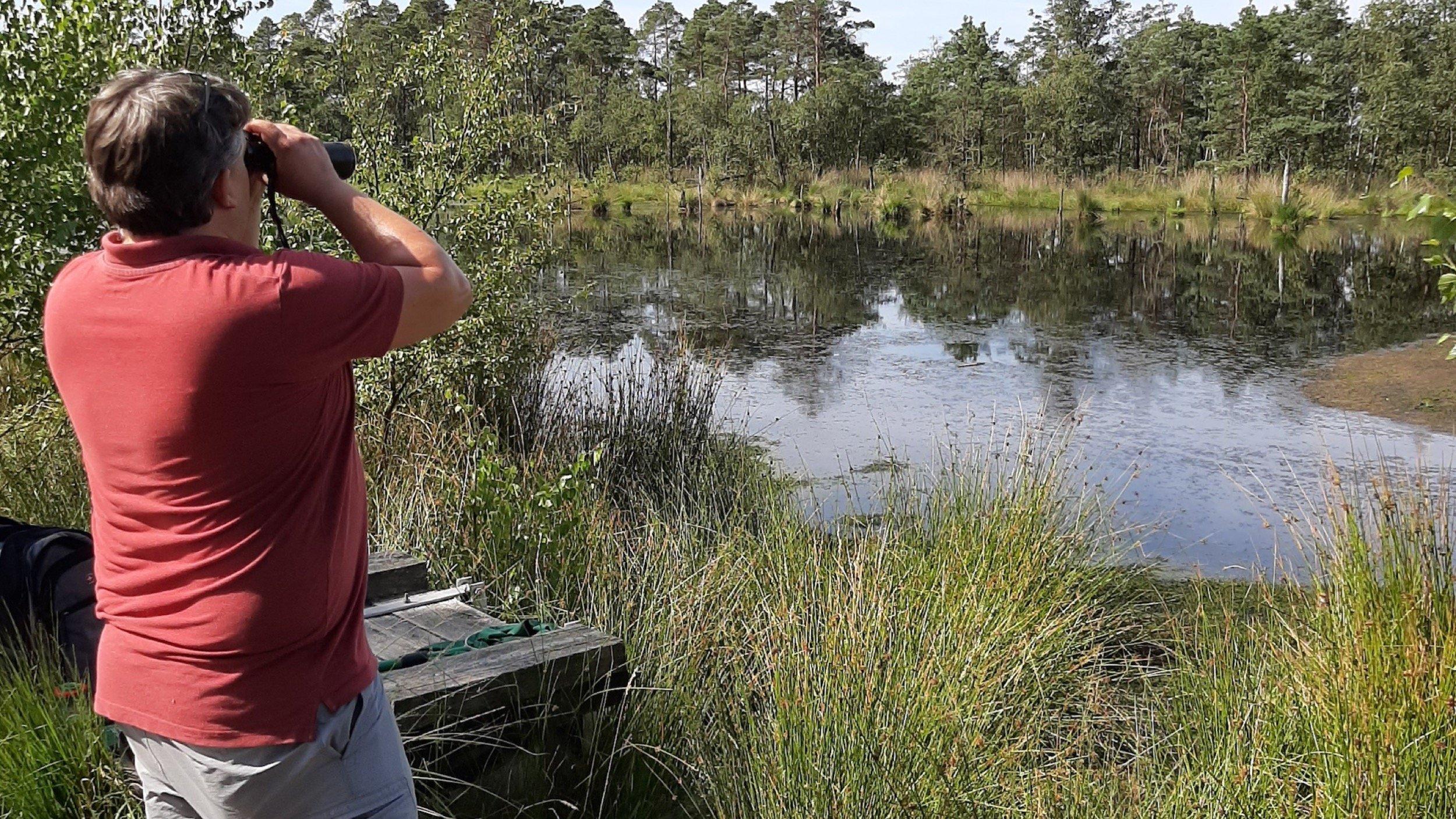 Eick von Ruschkowski steht vor einem Teich. Er schaut durch ein Fernglas.
