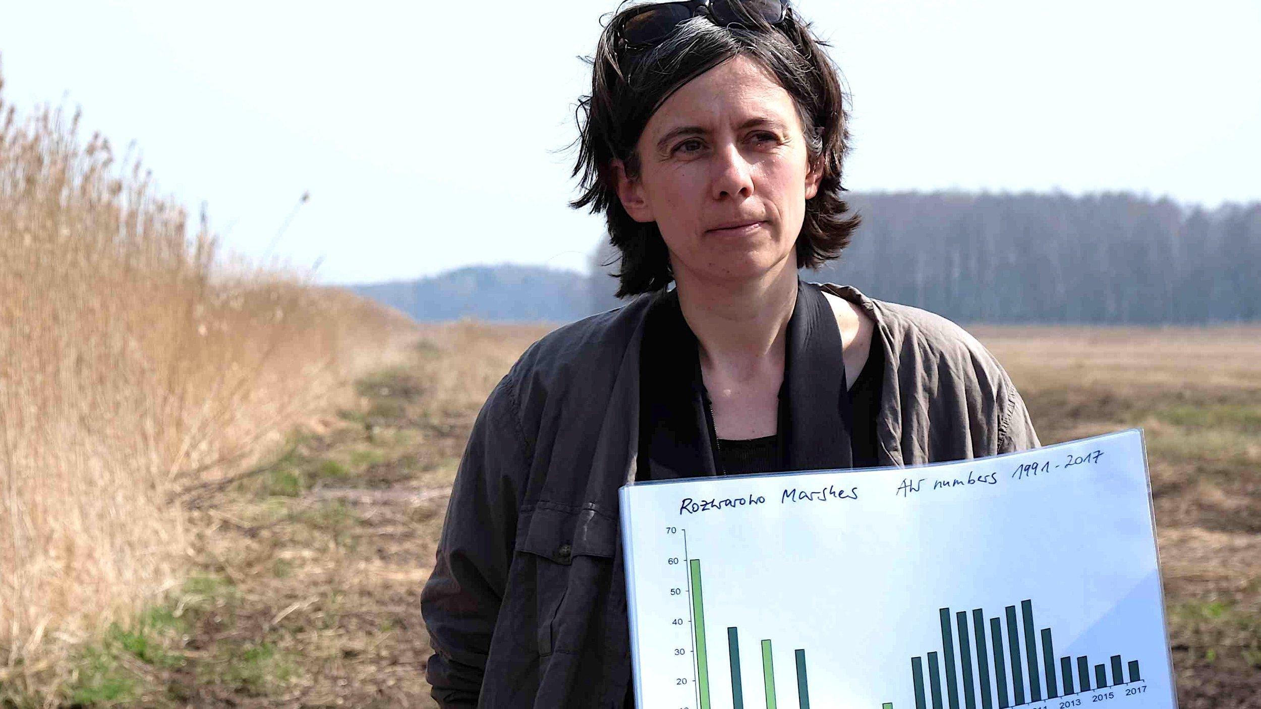 Foto von der Ornithologin und Moorexpertin Franziska Tanneberger. In der Hand hält sie ein Diagramm.