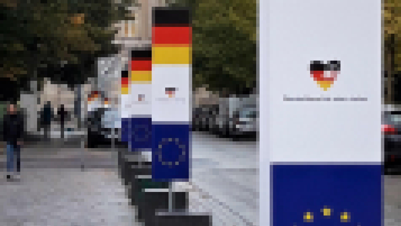 """An der Straße neben der Nikolaikirche hängen noch die Plakate mit den Deutschland- und Euopa-Farben und der Aufschrift """"Deutschland ist eins: vieles""""."""
