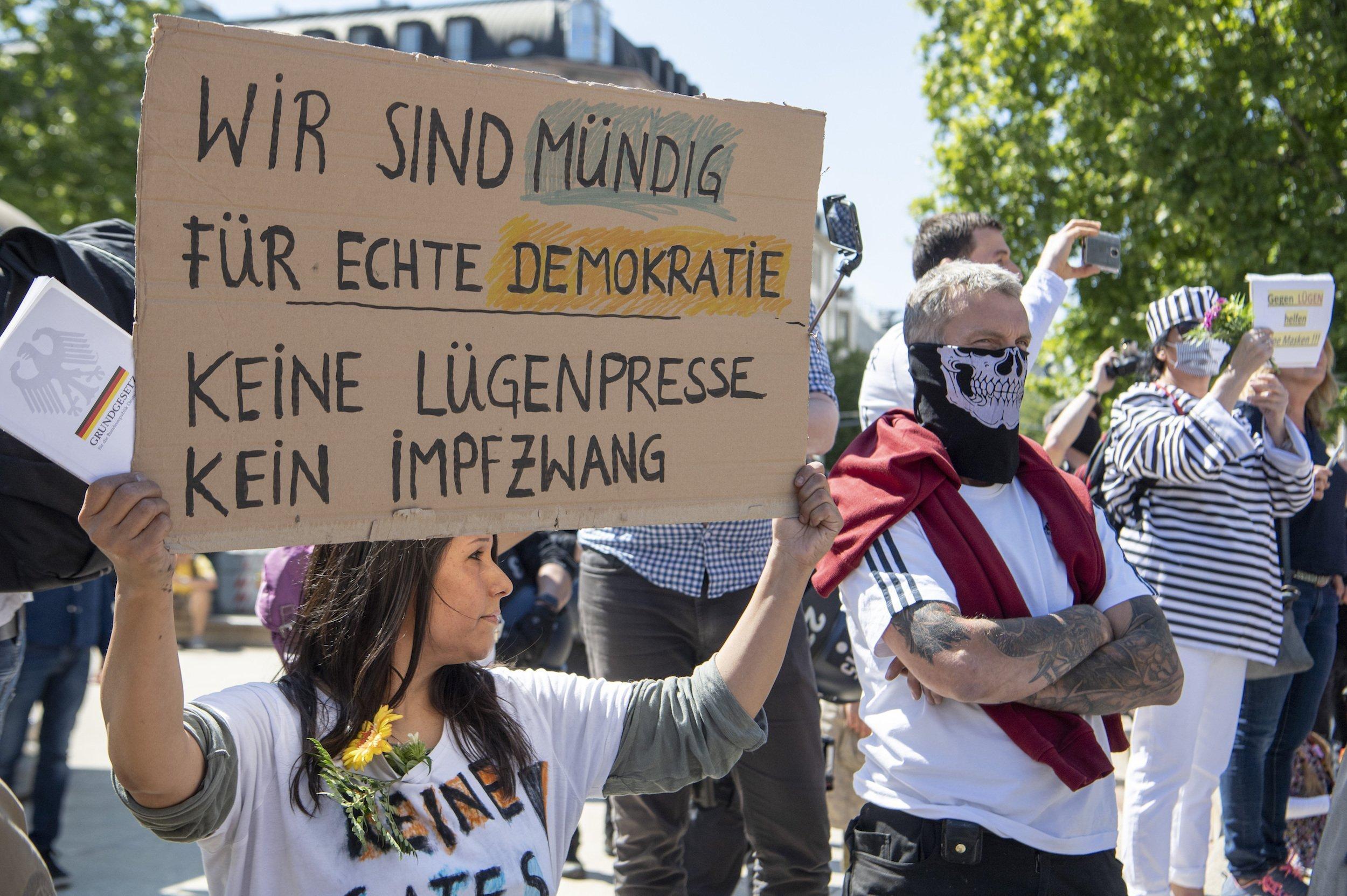 """Demonstrantinnen und Demonstranten. Eine Frau hält ein Pappschild hoch, auf dem steht: """"Wir sind mündig für echte Demokratie – Keine Lügenpresse. Kein Impfzwang"""". Neben ihr steht ein Mann, dessen untere Gesichtshälfte mit einem Tuch verdeckt ist, auf dem ein Totenschädel zu sehen ist. Daneben eine Person in Sträflingskleidung."""