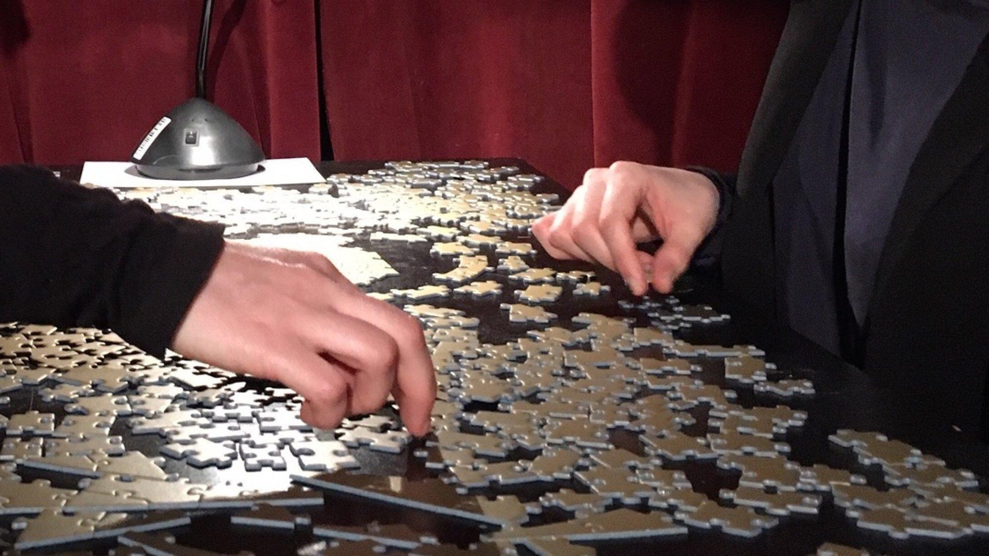 Zwei Menschen sitzen sich gegenüber und puzzlen gemeinsam. Man sieht nur ihre Hände. Die einfarbig goldenen Puzzleteile unterscheiden sich nur durch ihre Form.
