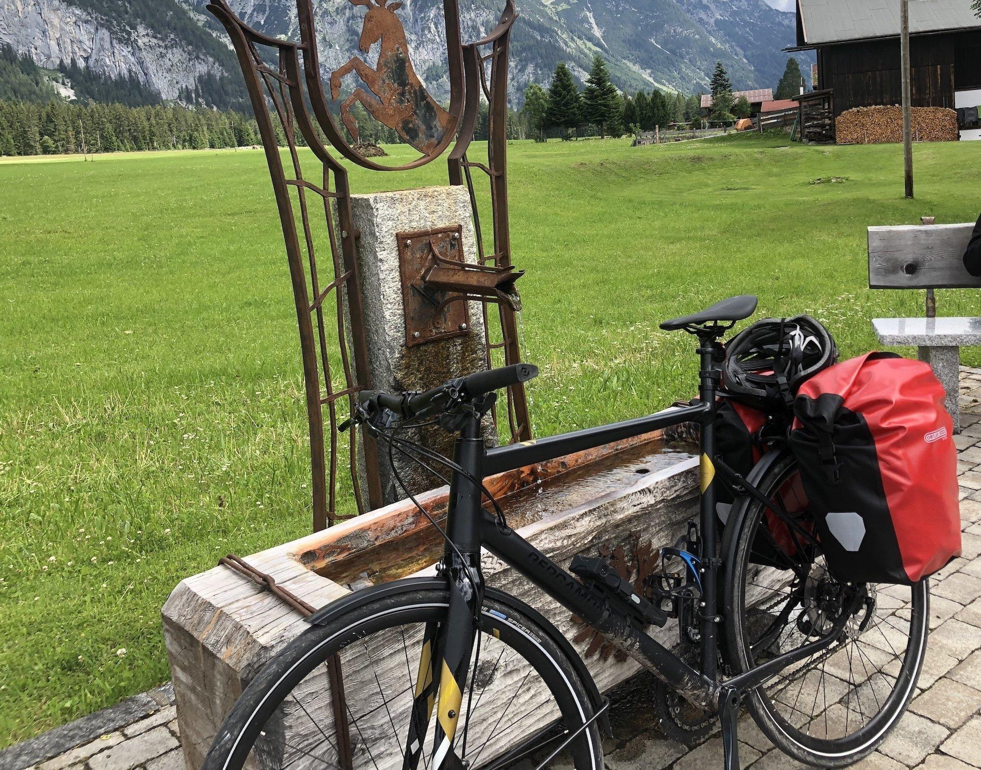 Dargestellt ist ein offener Brunnen in Tirol, aus dem Wasser fließt. Am Brunnen lehnt ein Fahrrad mit Gepäck.