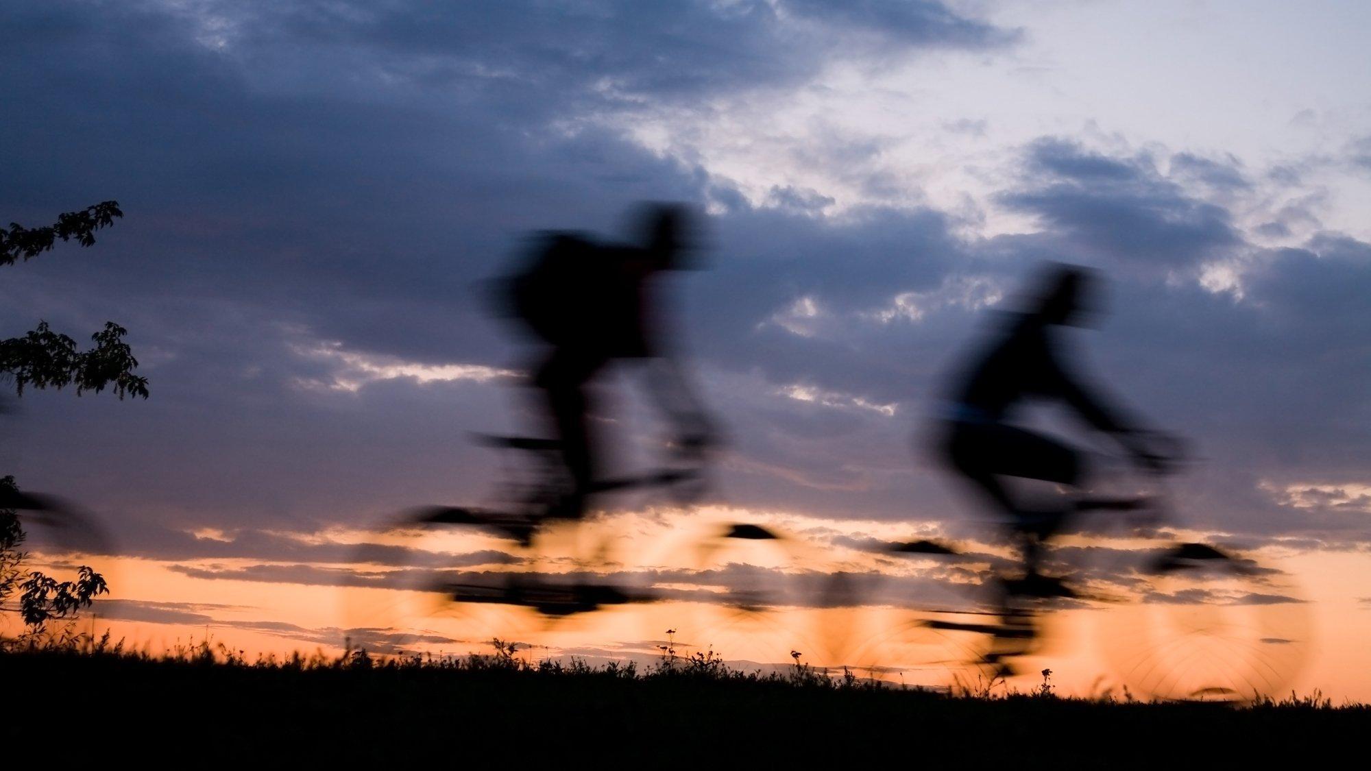 Das Bild zeigt die Umrisse von zwei Radfahrern im Abendlicht in freier Landschaft. Es vermittelt ein Gefühl der Freiheit, mit dem Fahrrad unterwegs zu sein.