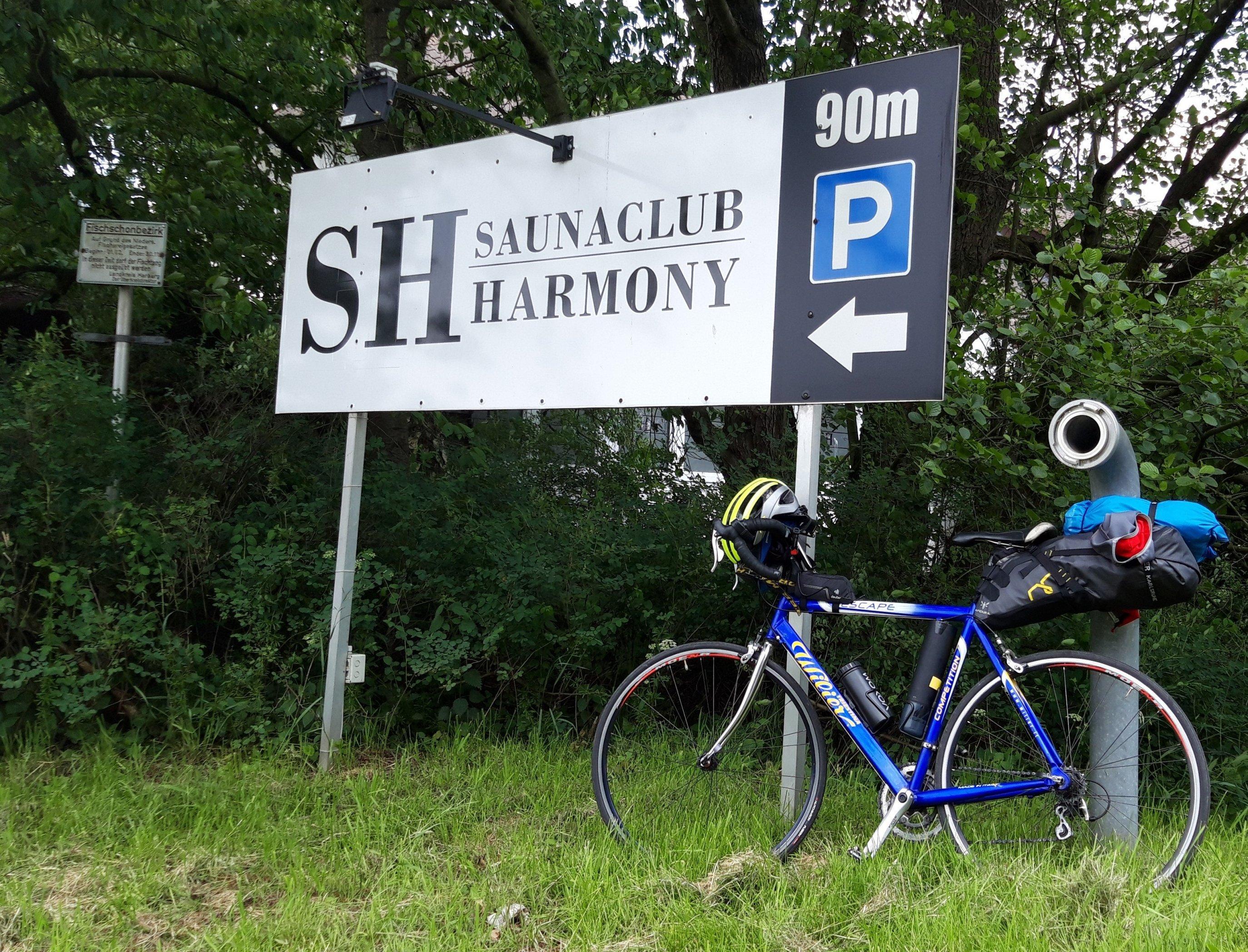 Das Vehikel des RadelndenReporters lehnt an einem Hinweisschild mit der Aufschrift Saunaclub Harmony.