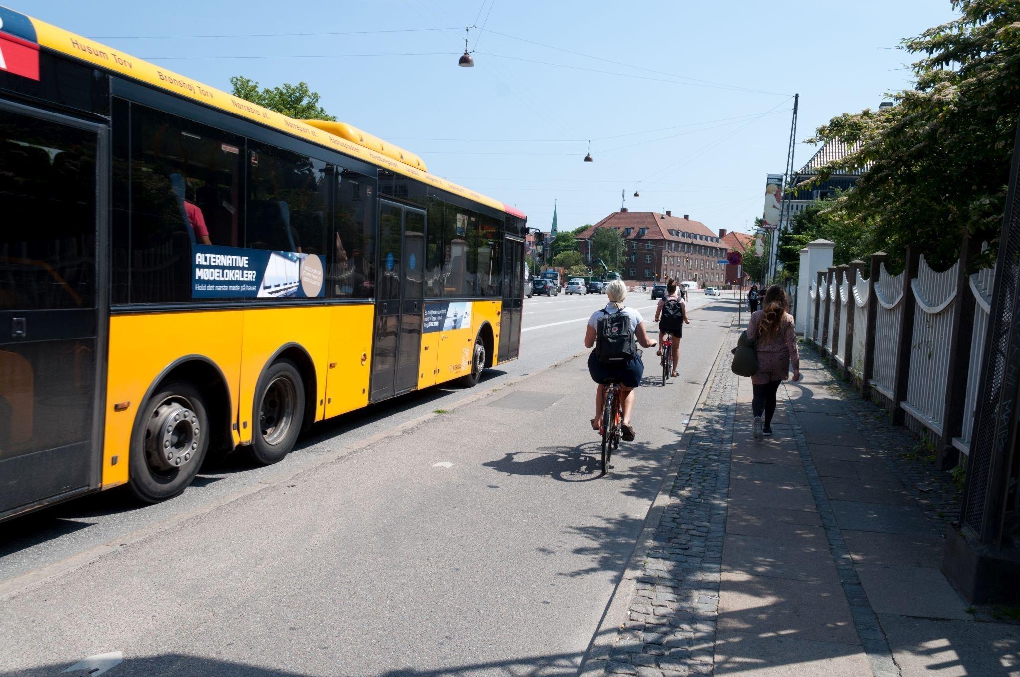 Ein Bus hält. Fahrradfahrer können sich auf einem breitem Radweg daneben vorbeifahren.