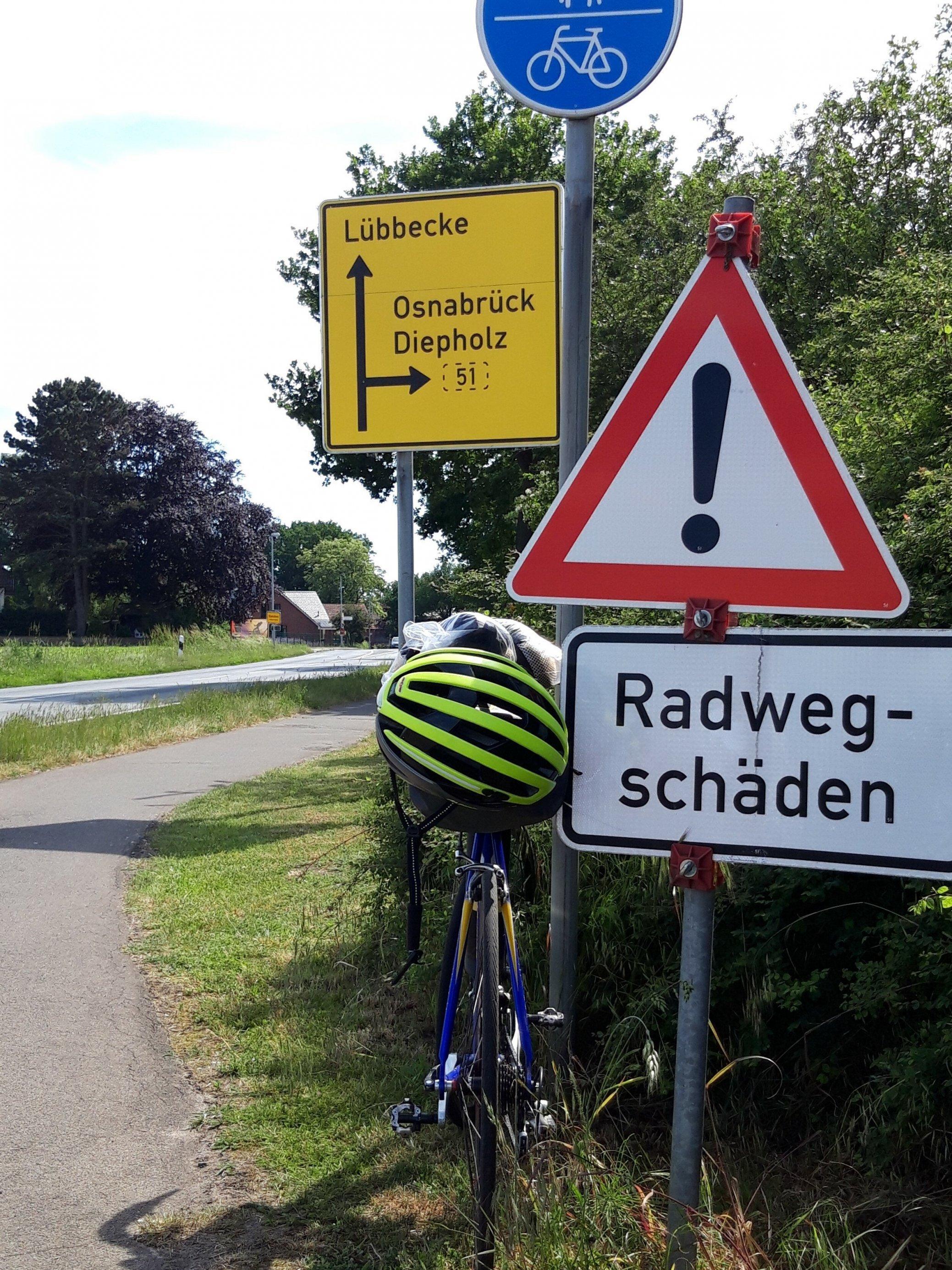 """Das Vehikel des RadelndenReporters lehnt an einem Warnschild mit der Aufschrift """"Radweg-Schäden""""."""