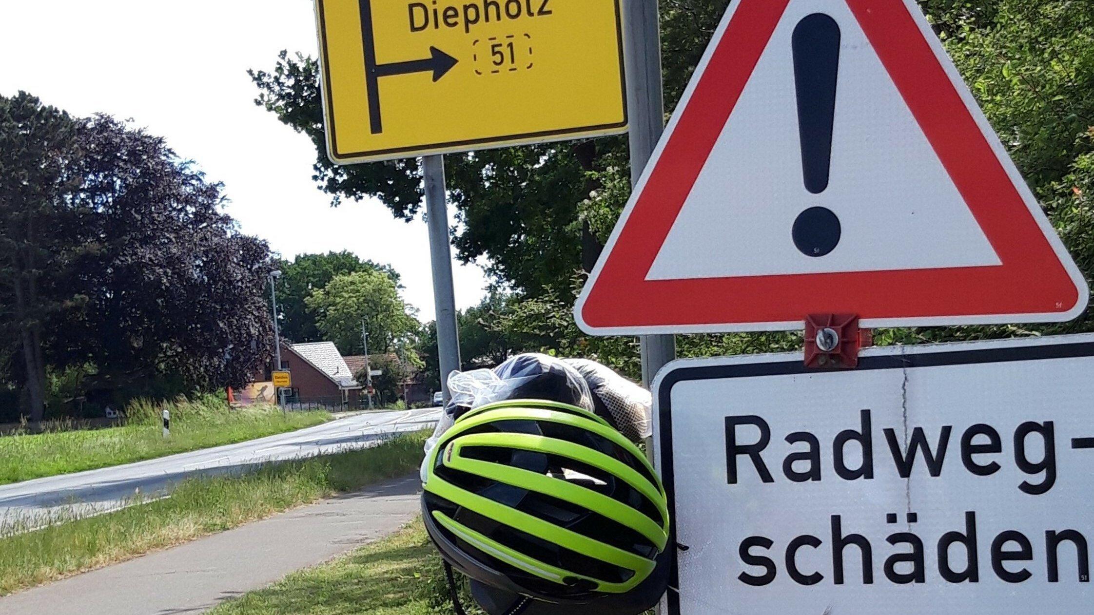 """Neben dem Radweg nördlich von Lübbecke prangt ein Warnschild mit der Aufschrift """"Radwege-Schäden""""."""