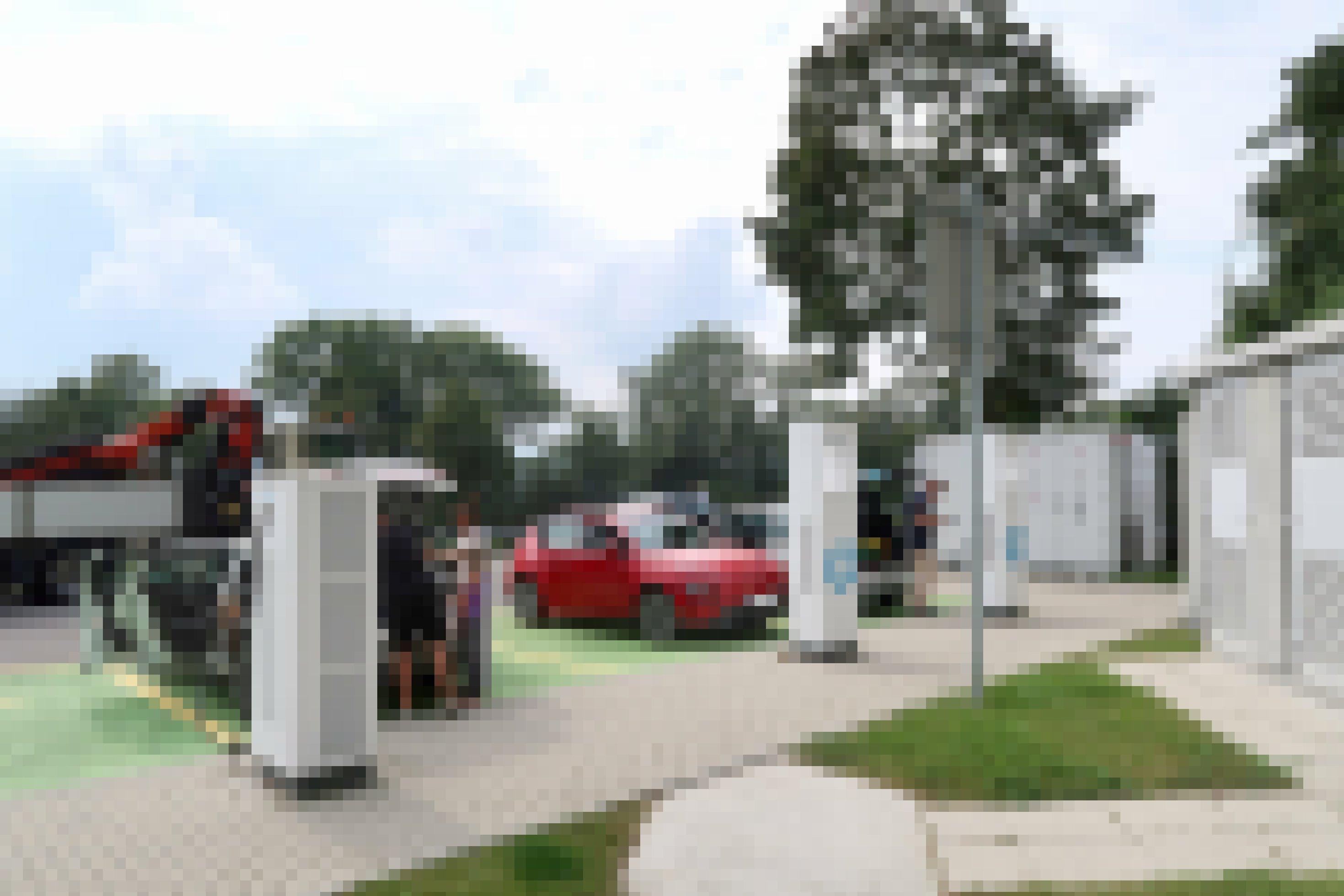 Drei Elektroautos laden Strom auf einem Parkplatz.