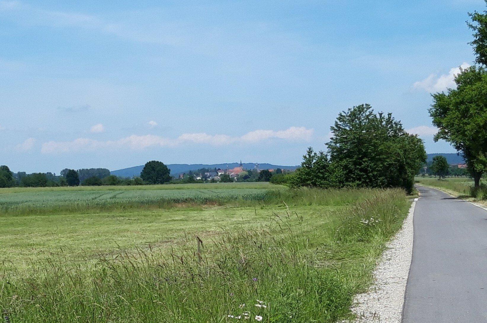 Am Horizont über Feld und Radweg heben sich vor einem Höhenzug die Dorfkirche sowie einige Häuser ab.