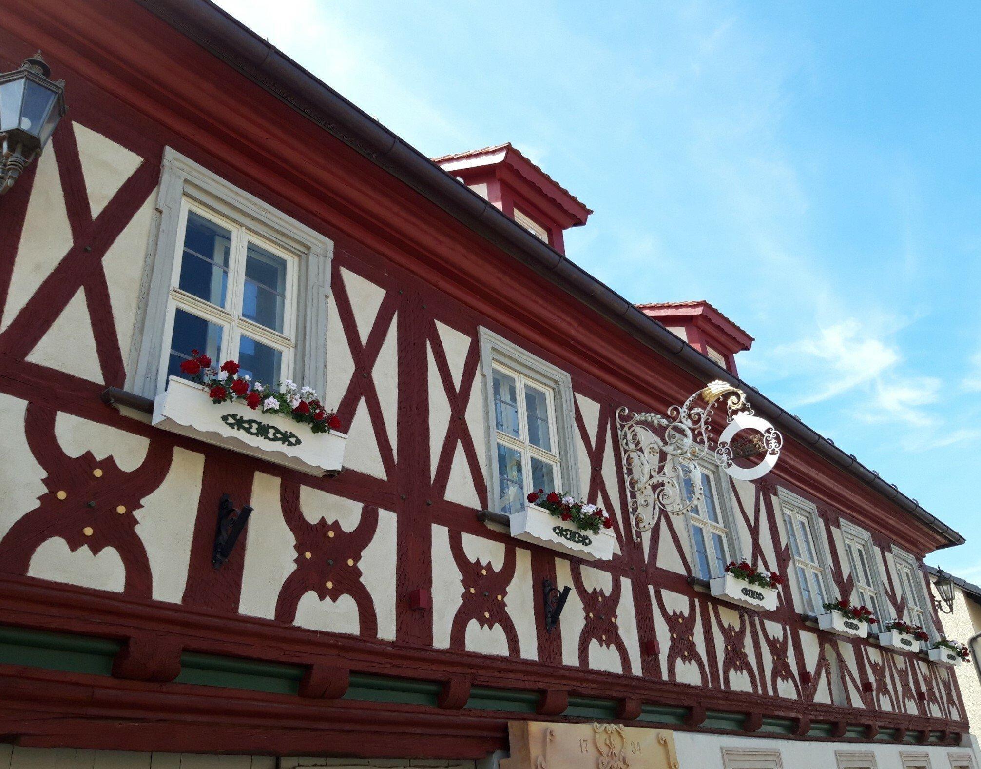 Sauber in rot gestrichen, korrespondiert das Holz der Außenfassade farblich mit den Geranien unter den kleinen schmucken Fenstern.