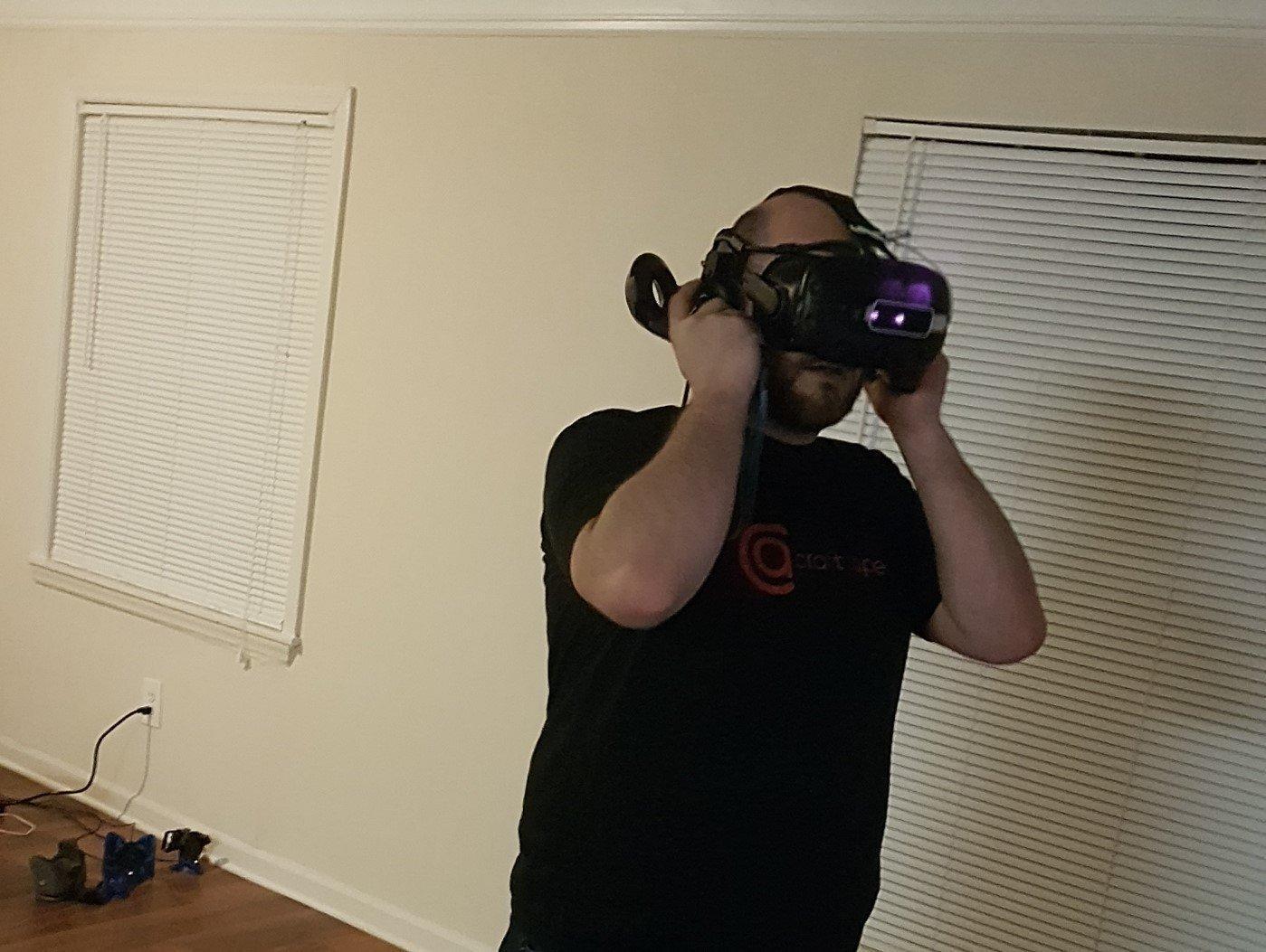 Ein junger Mann mit Vollbart und beginnender Glatze trägt eineine VR-Headset auf dem Kopf. Er steht in einem leeren, kahlen Raum. Die Jalousien vor den Fenstern sind geschlossen.