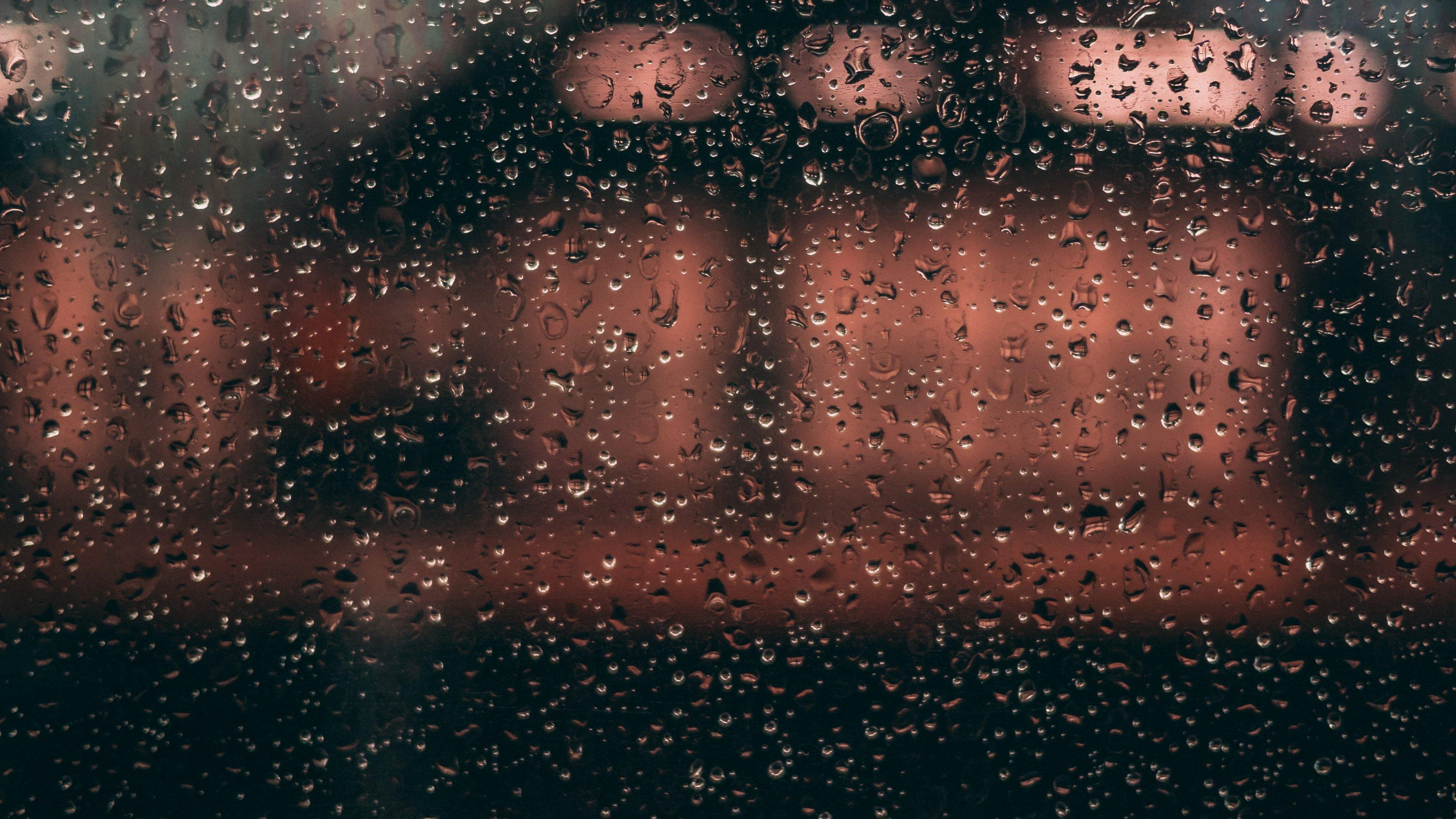 Durch eine mit Regentropfen übersäte Fensterscheibe sind unscharf die rötlichen Lichter zu erkennen, die auf einem nahen Gebäude scheinen. das Bild vermittelt das Gefühl von Isoliertheit und Abgeschiedenheit.