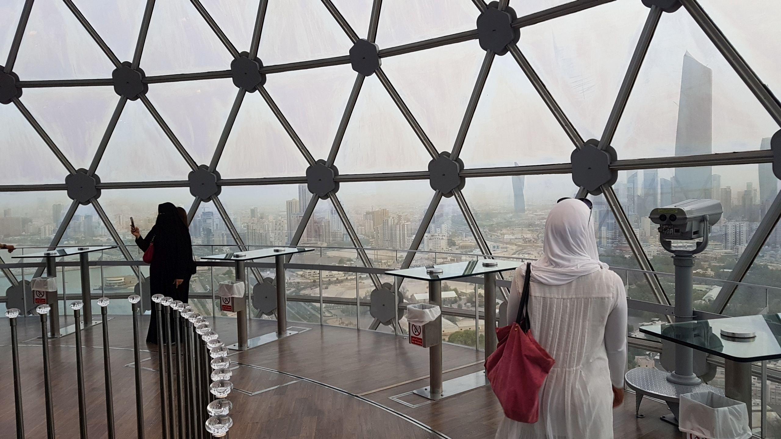 Sana steht mit dem Rücken zur Kamera unter der riesigen Glaskuppel einer Aussichtsplattform. Von dort oben kann man große Teile Kuwaits sehen.