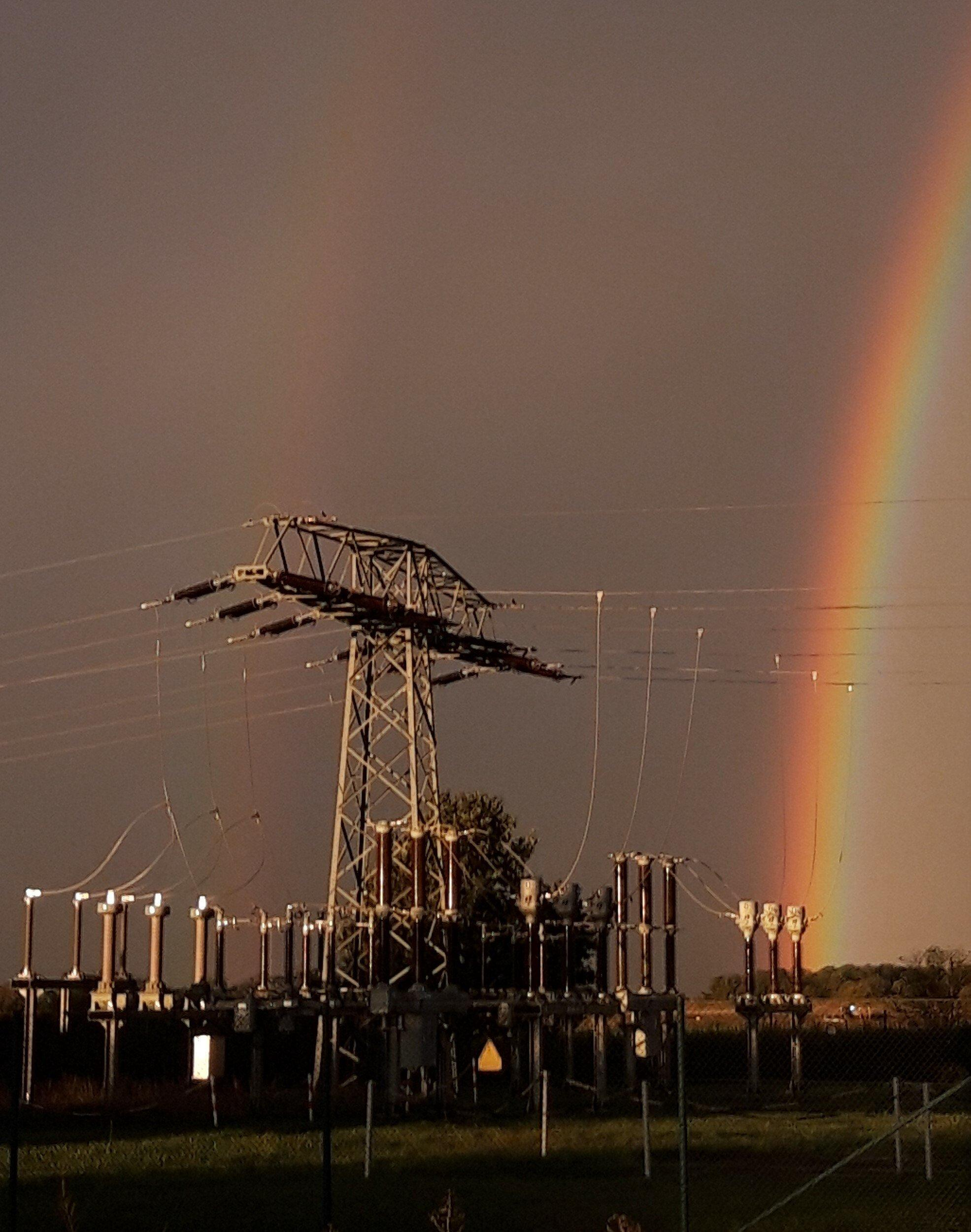 Neben den Transformatoren eines Umspannwerks strahlt vor dunklem Grau-Braun ein Regenbogen.