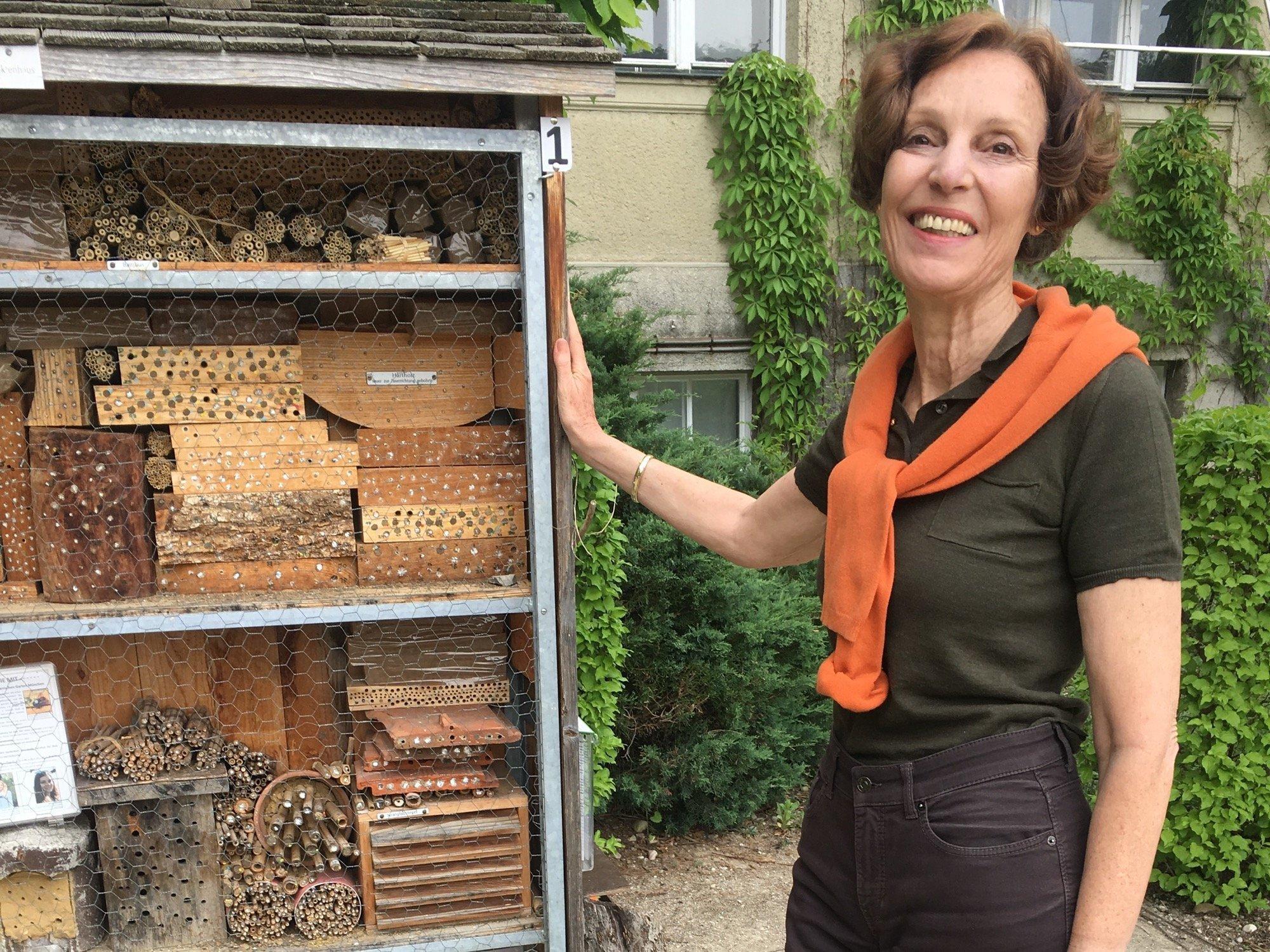 Susanne S. Renner steht neben einem Insektenhotel.