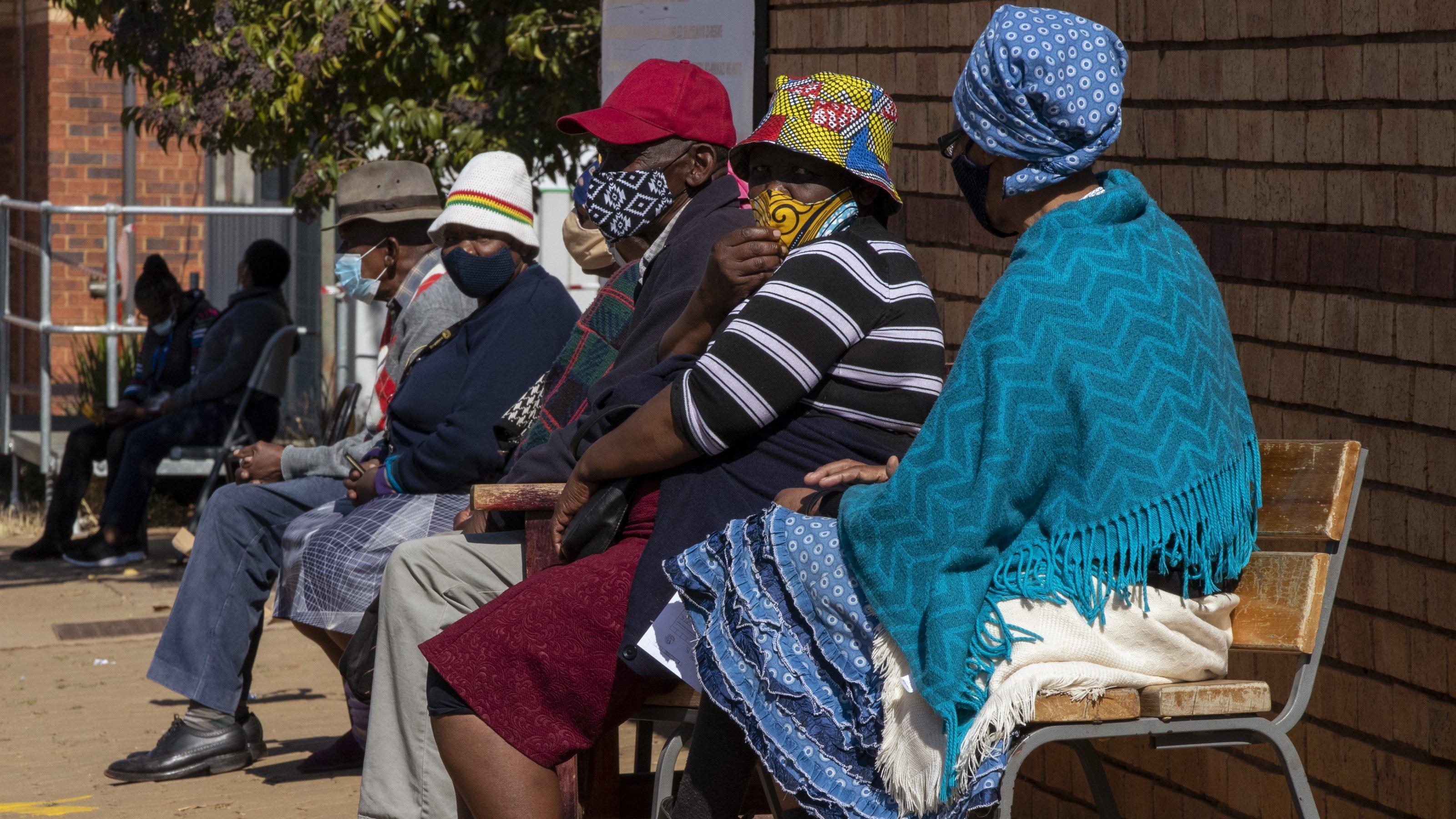 Frauen und Männer mit farbenfrohen Gesichtsmasken sitzen auf Stühlen vor der Klinik in der Schlange