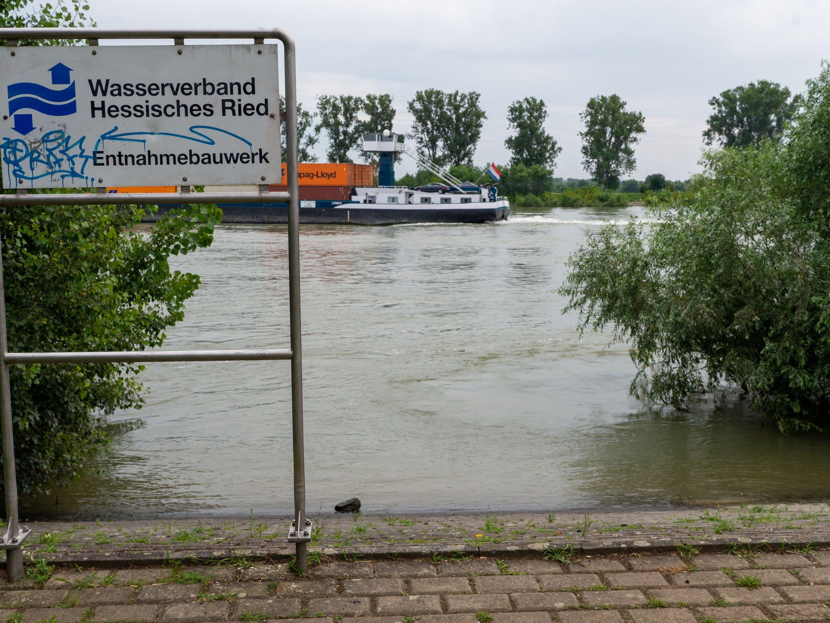 """Schild """"Entnahmebauwerk"""" direkt am Rheinufer, Auf dem Fluss fährt ein Schiff zum linken Bildrand"""