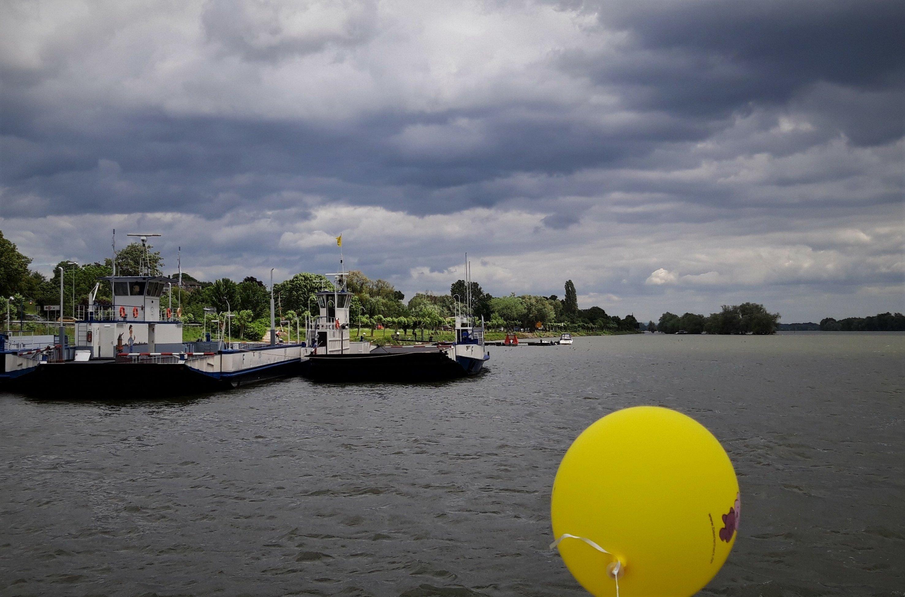 Hinter einem gelben Luftballon ist unter bleischwarzem Himmel das dunkle Rehinwasser zu sehen, auf dem eine Rheinfähre dümpelt.