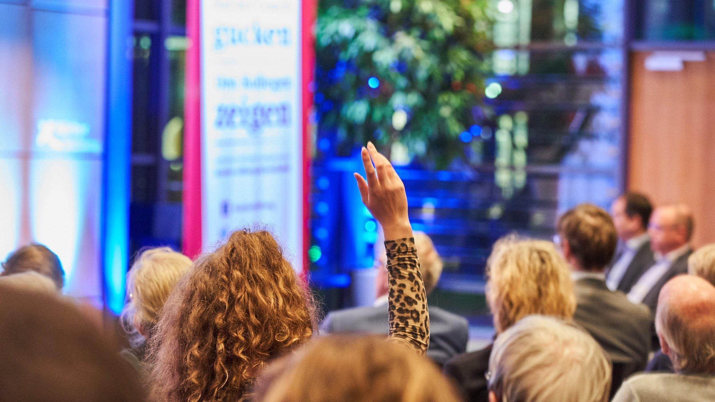 Eine Frau hebt bei einer Veranstaltung die Hand, um zu Wort zu kommen
