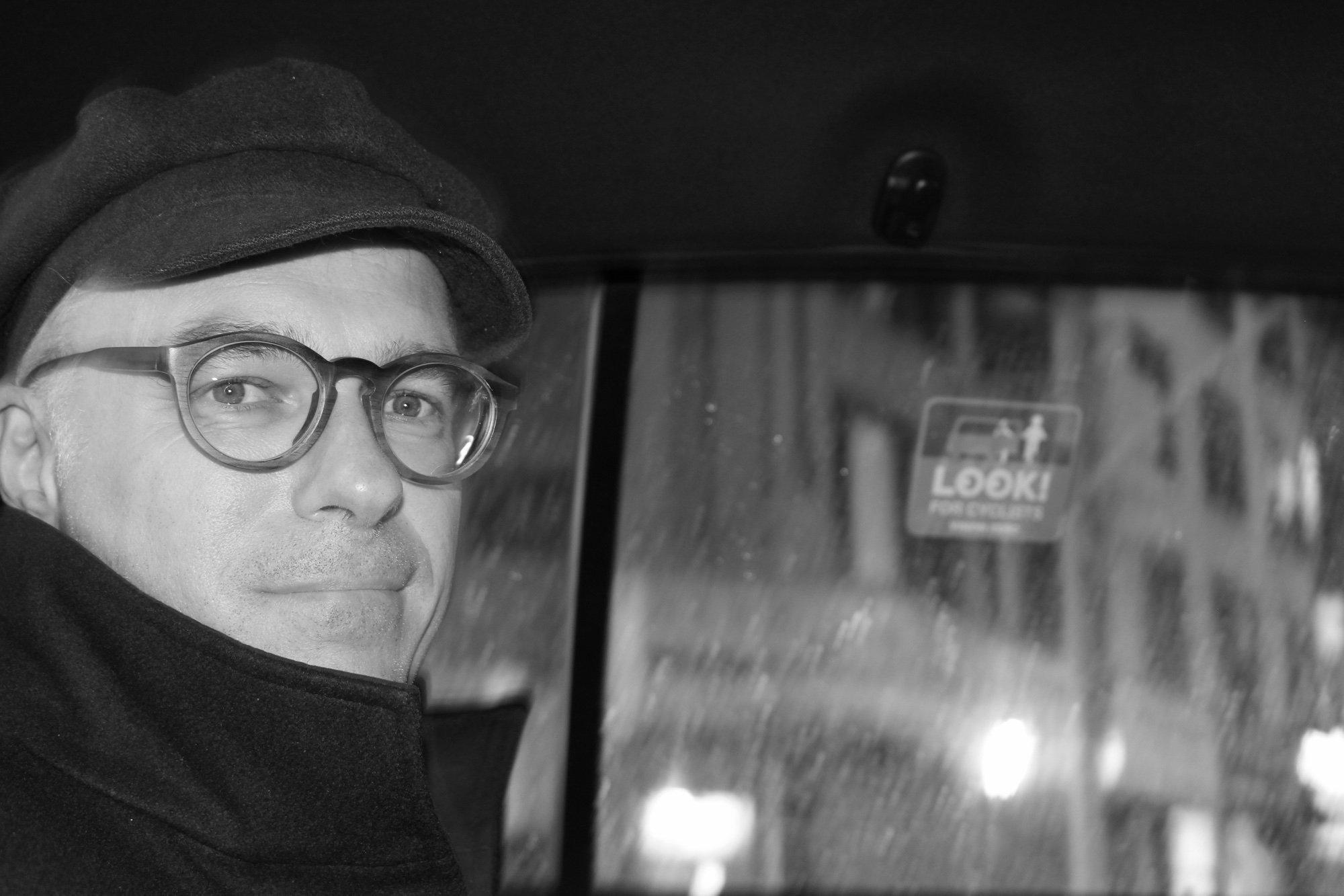 Schwarz-weiß Aufnahme von Andreas von Bubnoff. Er sitzt bei Regen in einem Auto und trägt eine Mütze, Brille und einen Mantel.