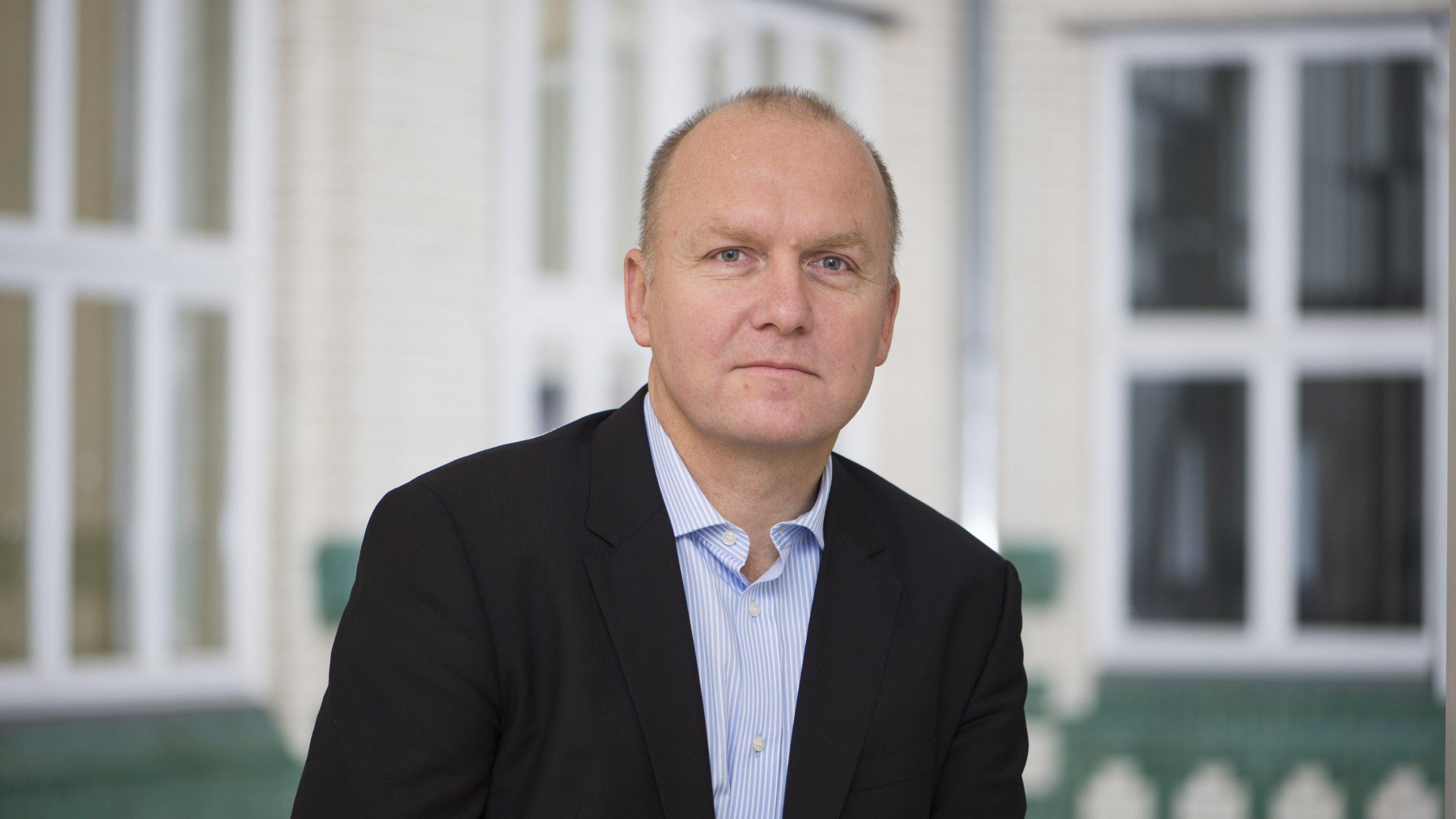 Andreas Rinke steht vor einer Wand.
