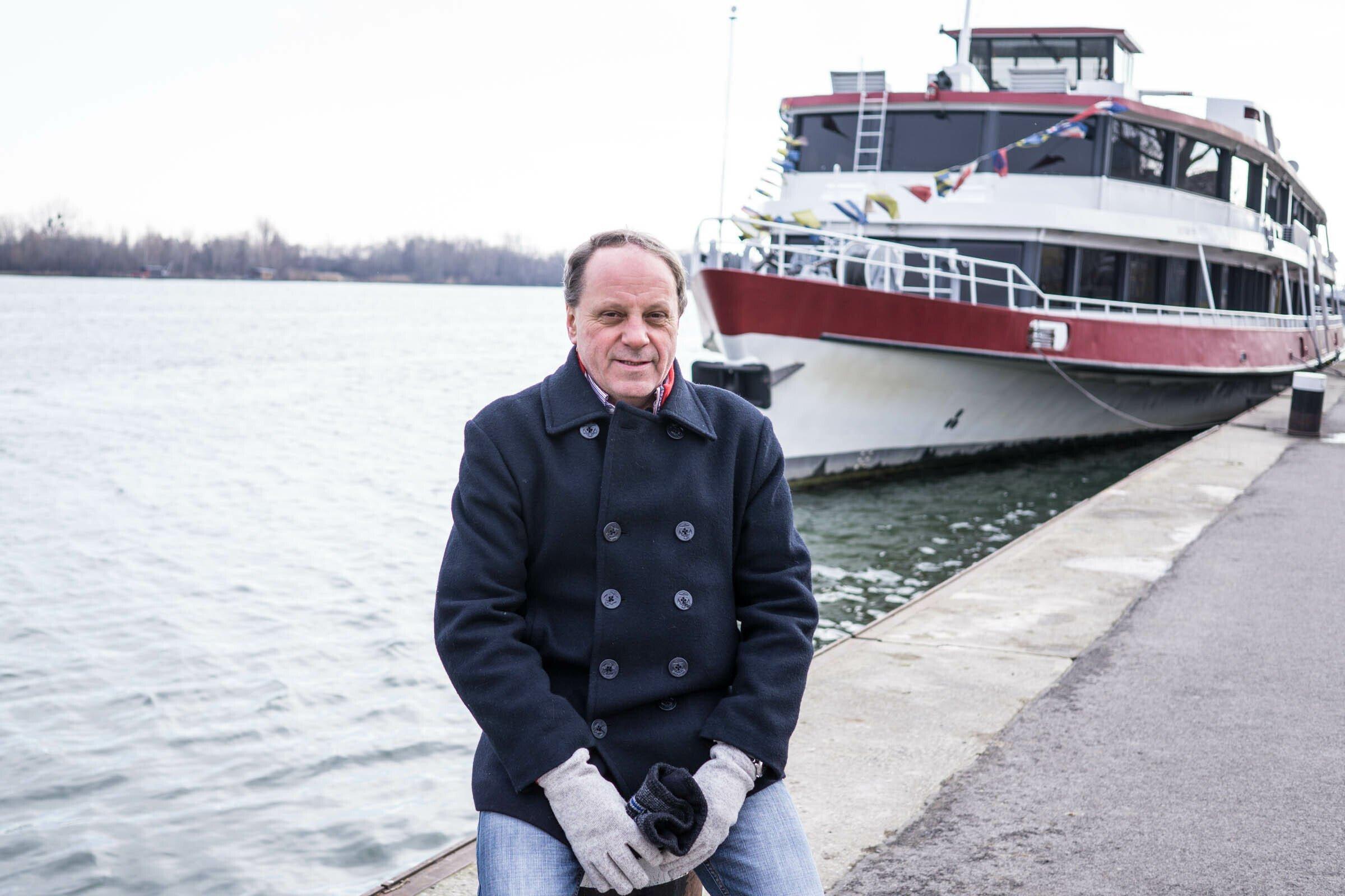 Ein Mann sitzt im Hafen der Donau in Wien auf einem Poller.