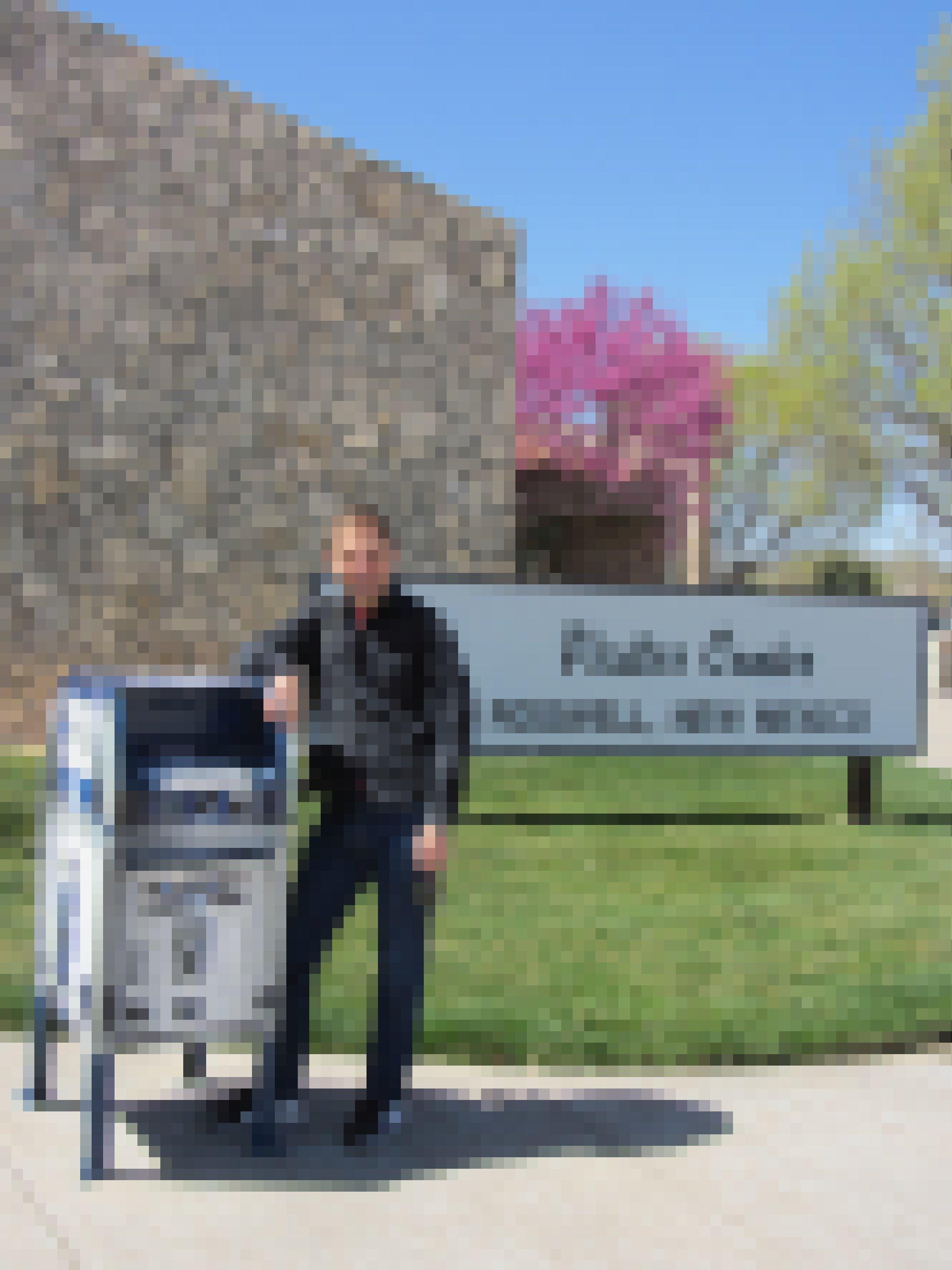 """Ein junger Mann steht neben einem Briefkasten, der wie der Roboter """"R2D2"""" aus Star Wars aussieht."""