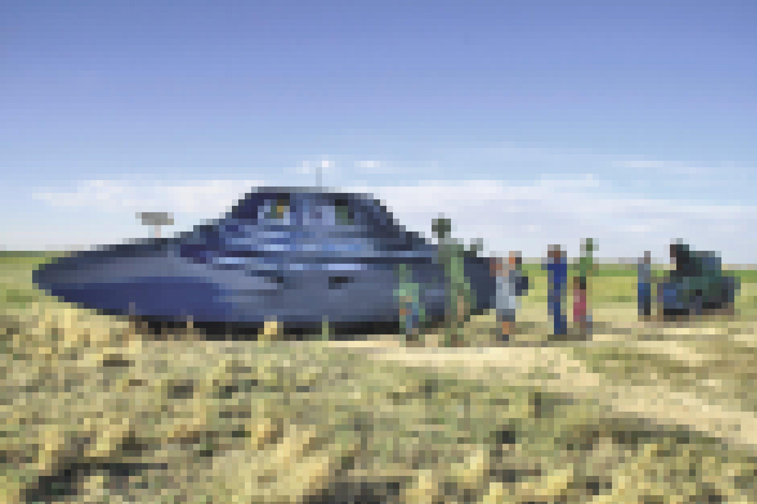 """Ein Ufo aus Pappe liegt auf einem Feld. Daneben stehen Pappfiguren, die wie Farmer aussehen und dem Ufo """"Starthilfe"""" geben."""