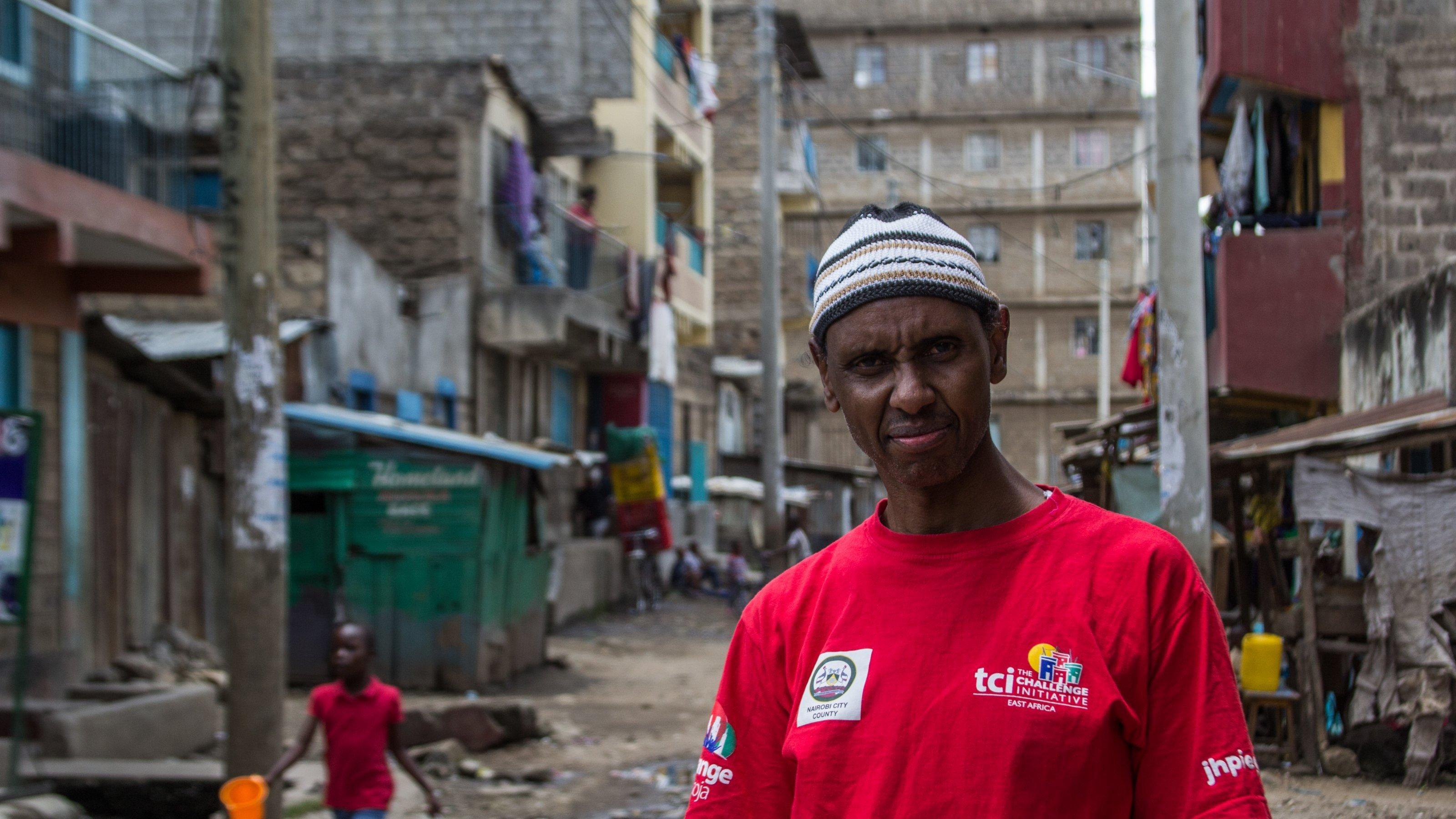 Im Vordergrund steht Salat Hamud, in einem roten T-Shirt und mit einer Mütze. Im Hintergrund sieht man mehrstöckige Häuser mit viel Wäsche zum Trocknen, und im Mittelgrund ein kleines Mädchen, das Wasser schleppt.
