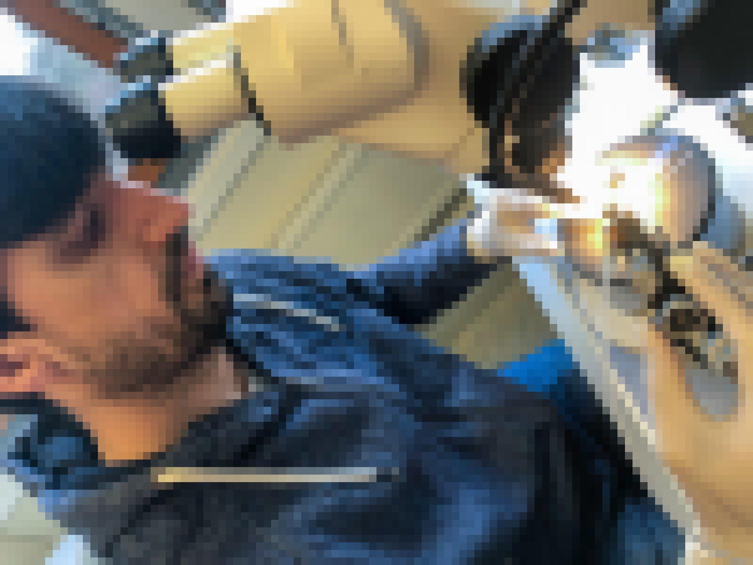 Ein Mann sitzt vor einem Binokular. Er bedient eine Spritze, die von einem Stabilisator gehalten wird.